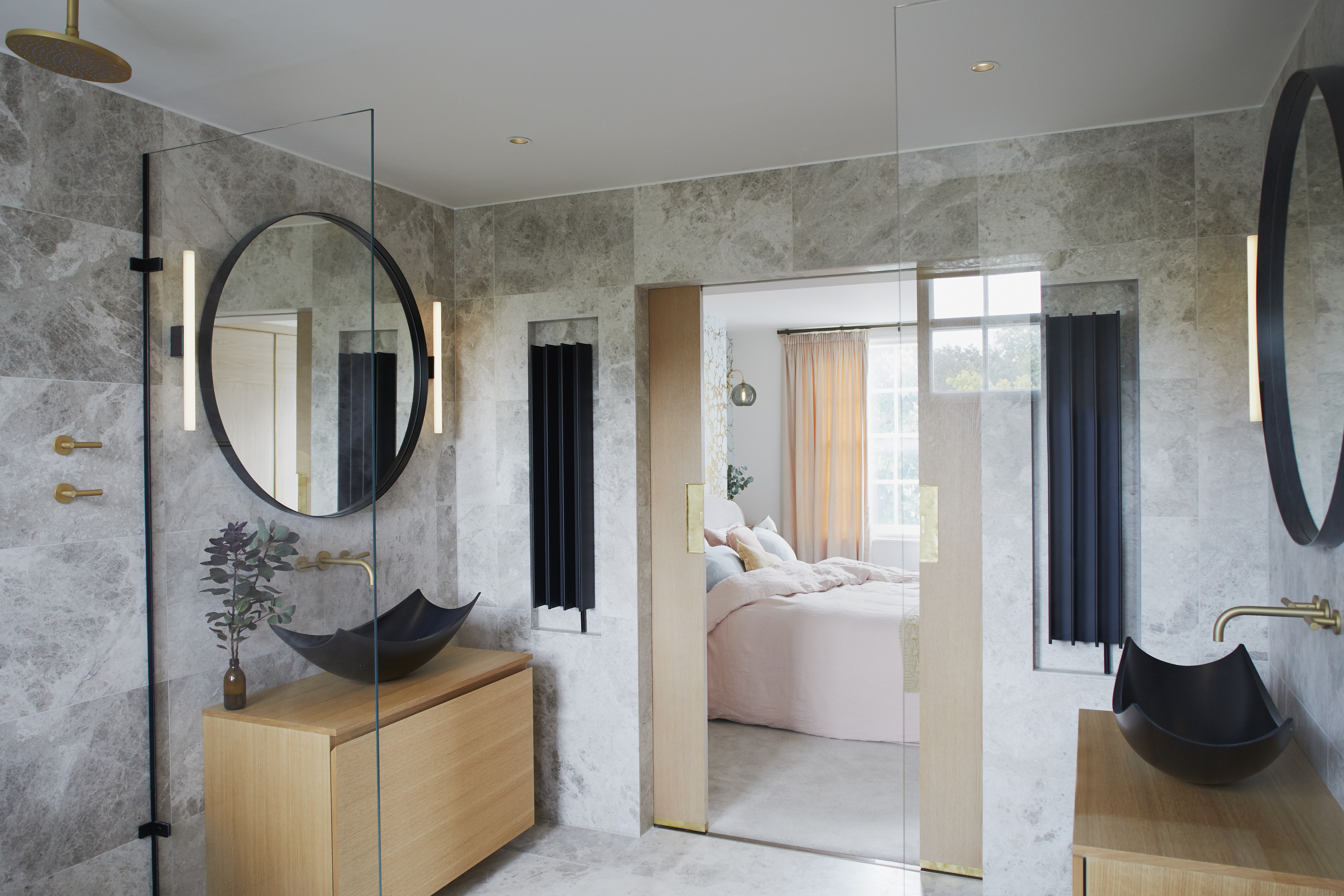 black basin sinks in en suite bathroom with marble walls