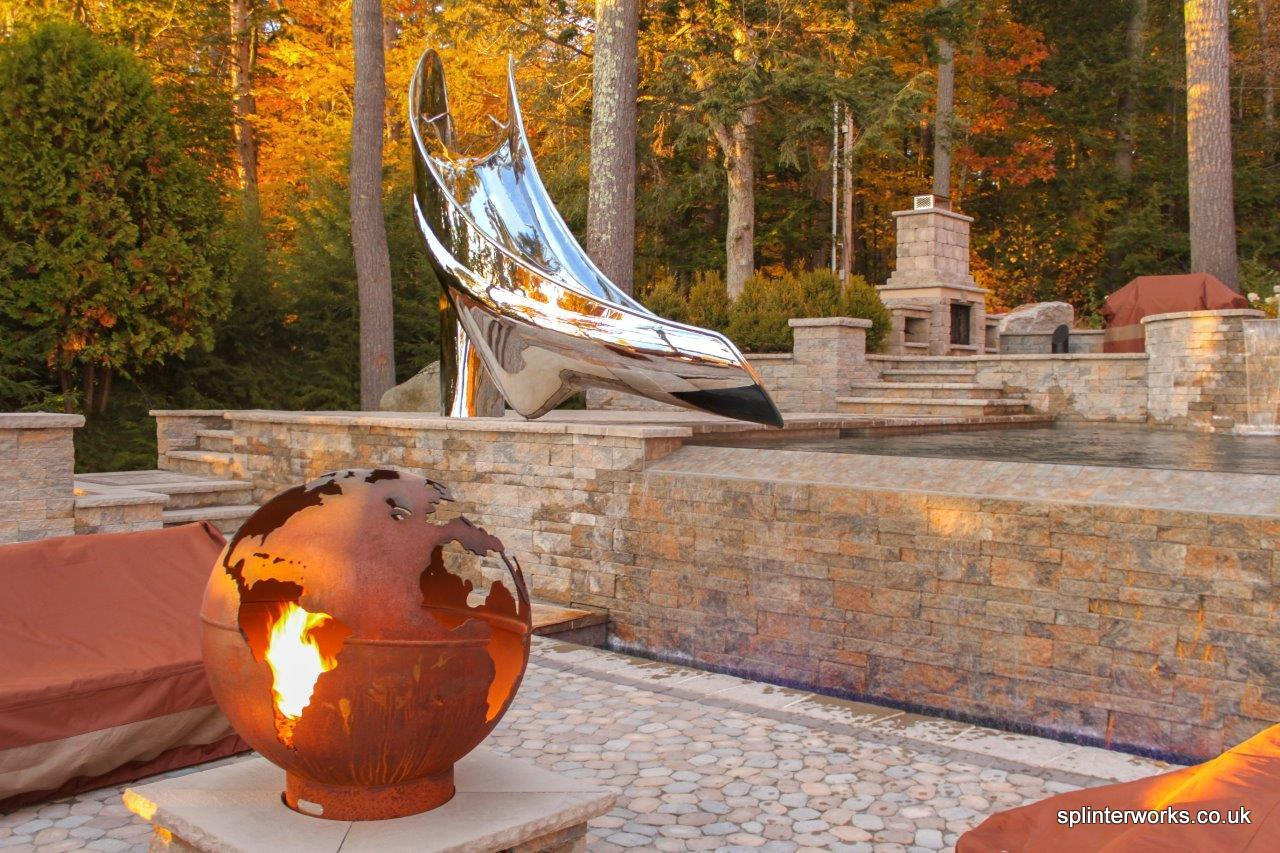 Sculptural pool slide beside lake with fire pit