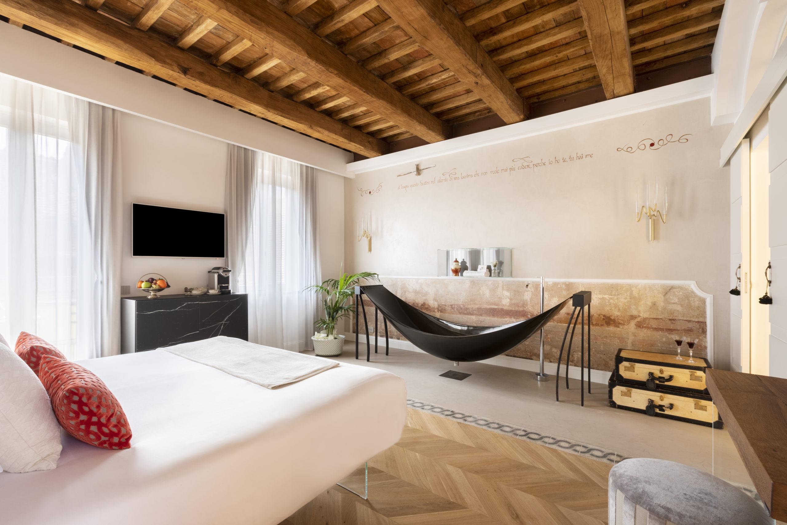 Black carbon fiber hammock bath in white hotel room, at Hotel Poesis