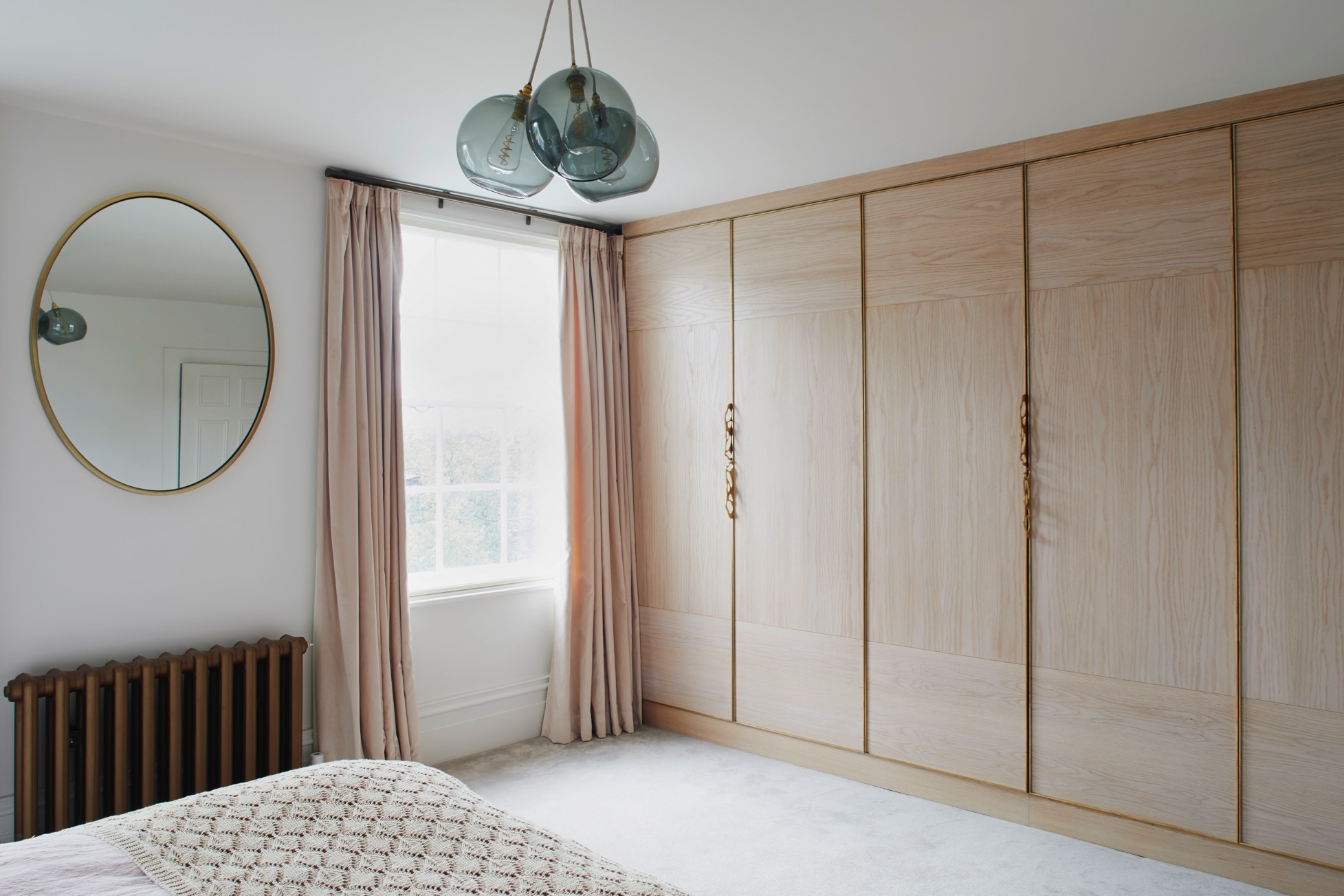Bespoke bedroom cabinetry in soft pink with brass handles and details