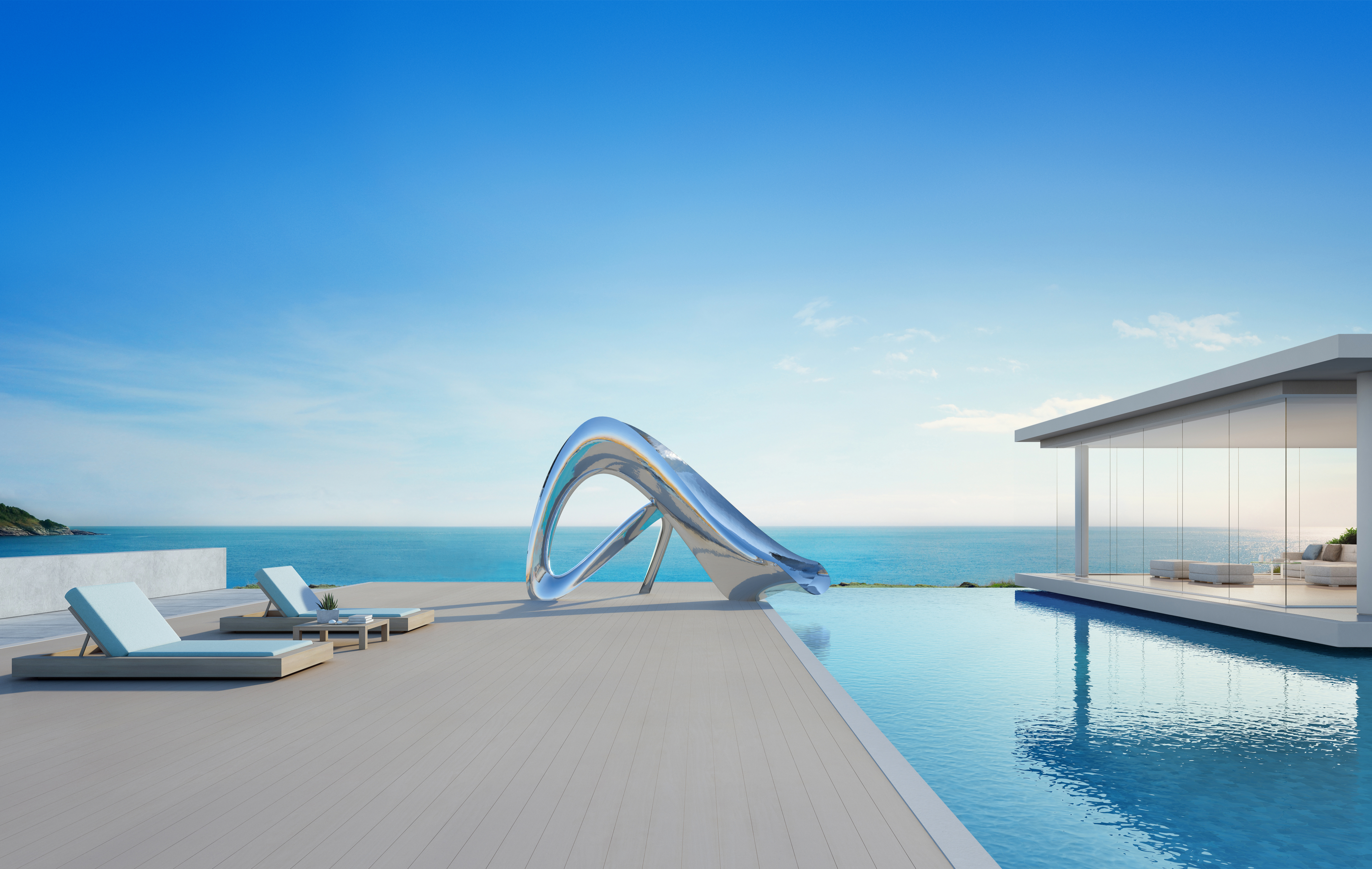 Sculptural pool side slide next to ocean view pool and modern house