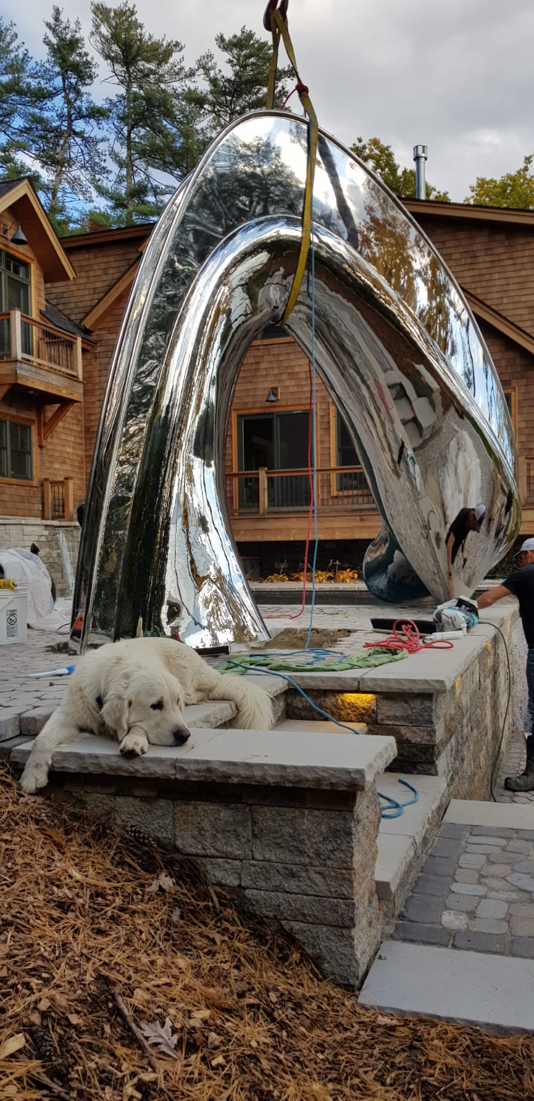 Outdoor family pool slide being installed at lake-house with dog