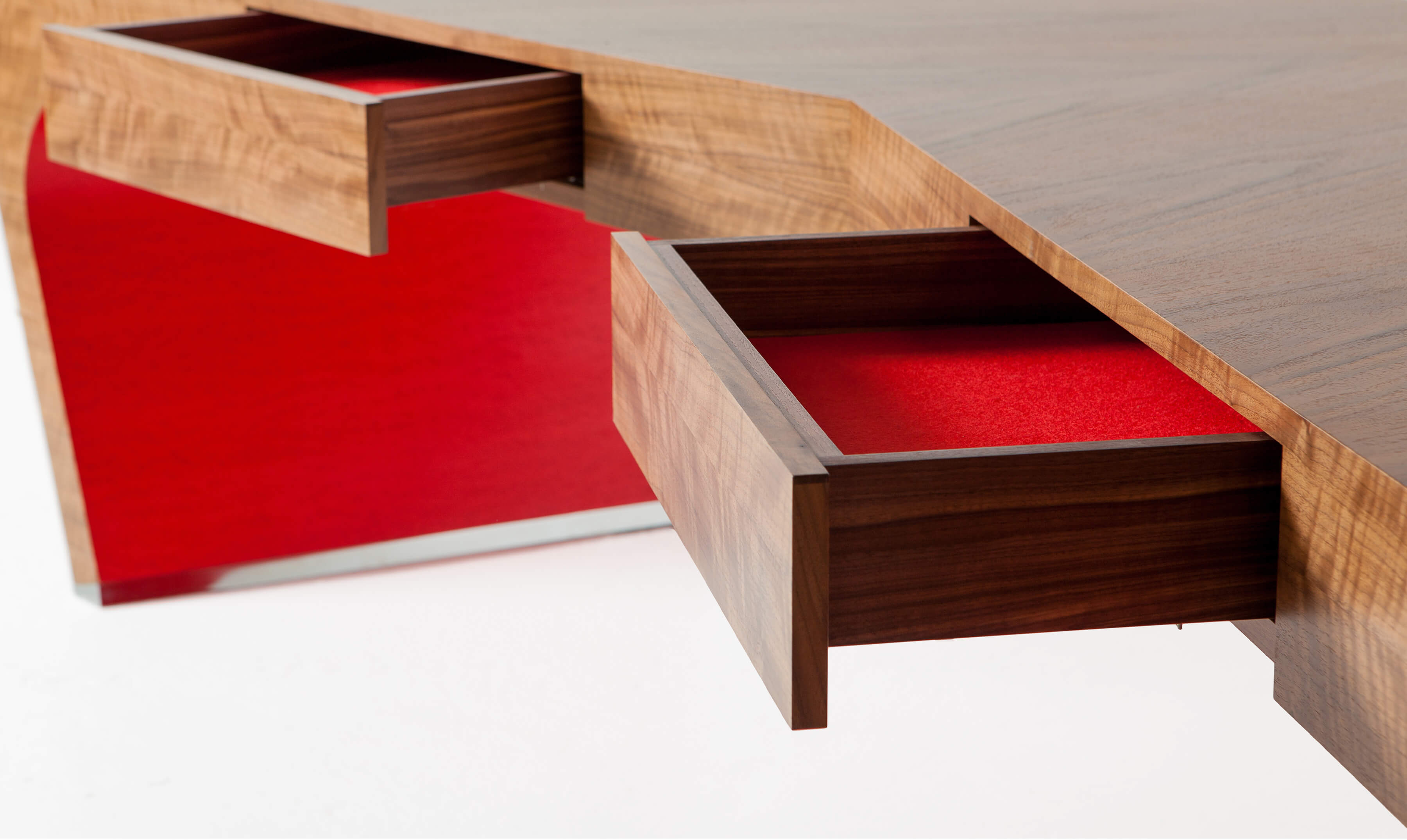 Red detail on empowering hand-crafted desk in v-shaped design