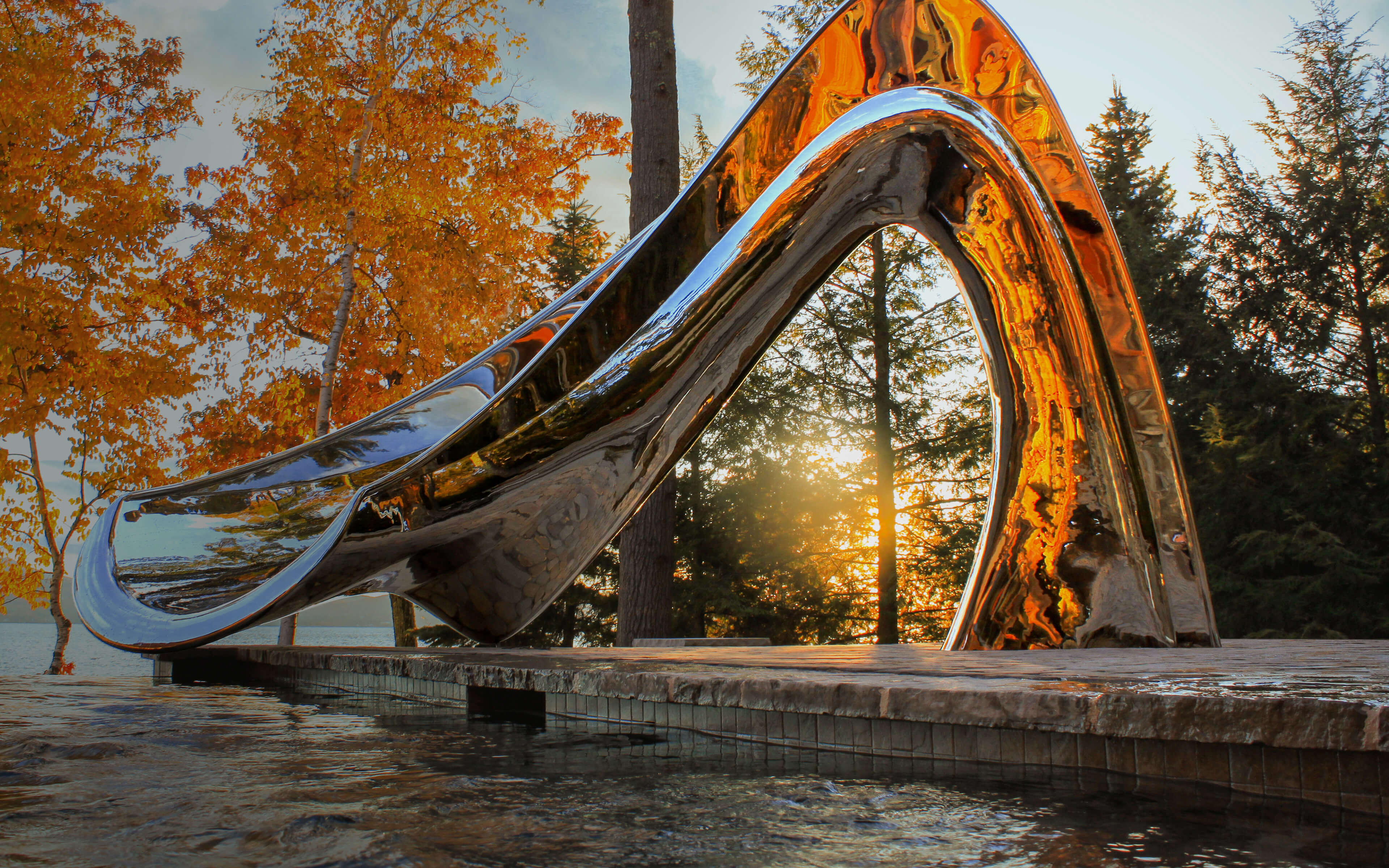 Sculptural pool slide in mirror polished metal next to lake at sunset, in collaboration with water shape designer