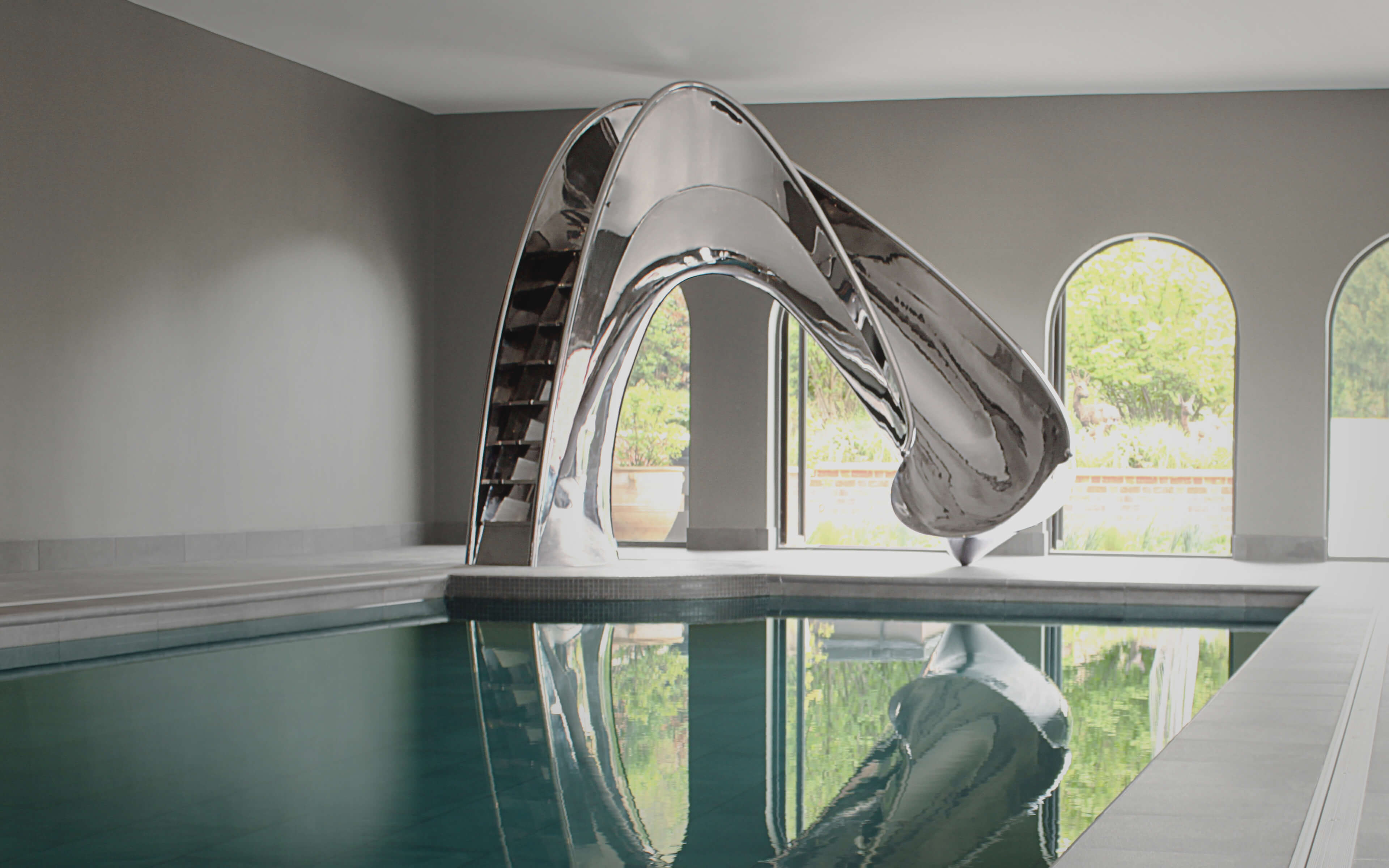 Mirror polished stainless steel pool slide in architectural pool pavilion.