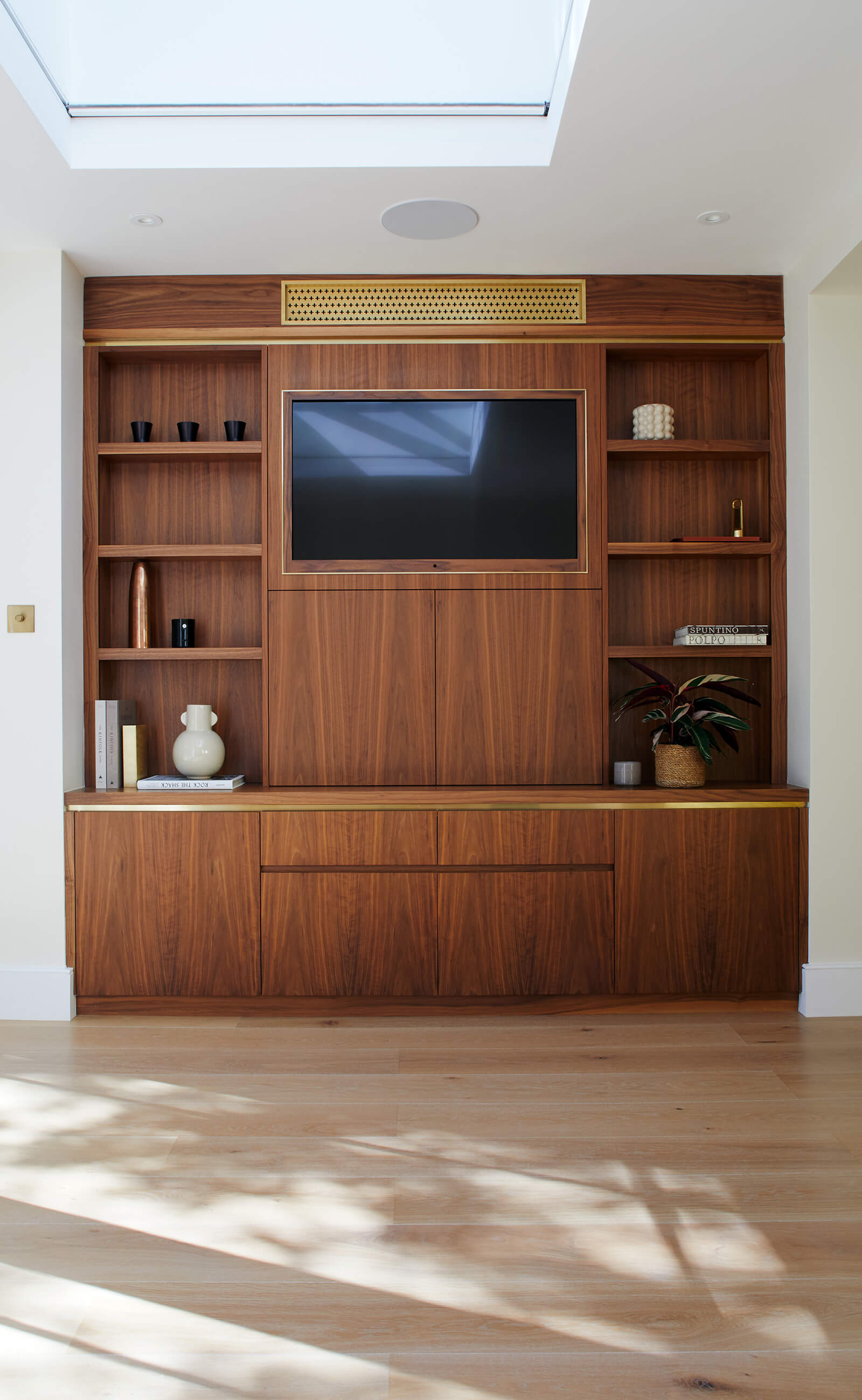 Bespoke walnut cabinetry for TV and air conditioning with brass detail