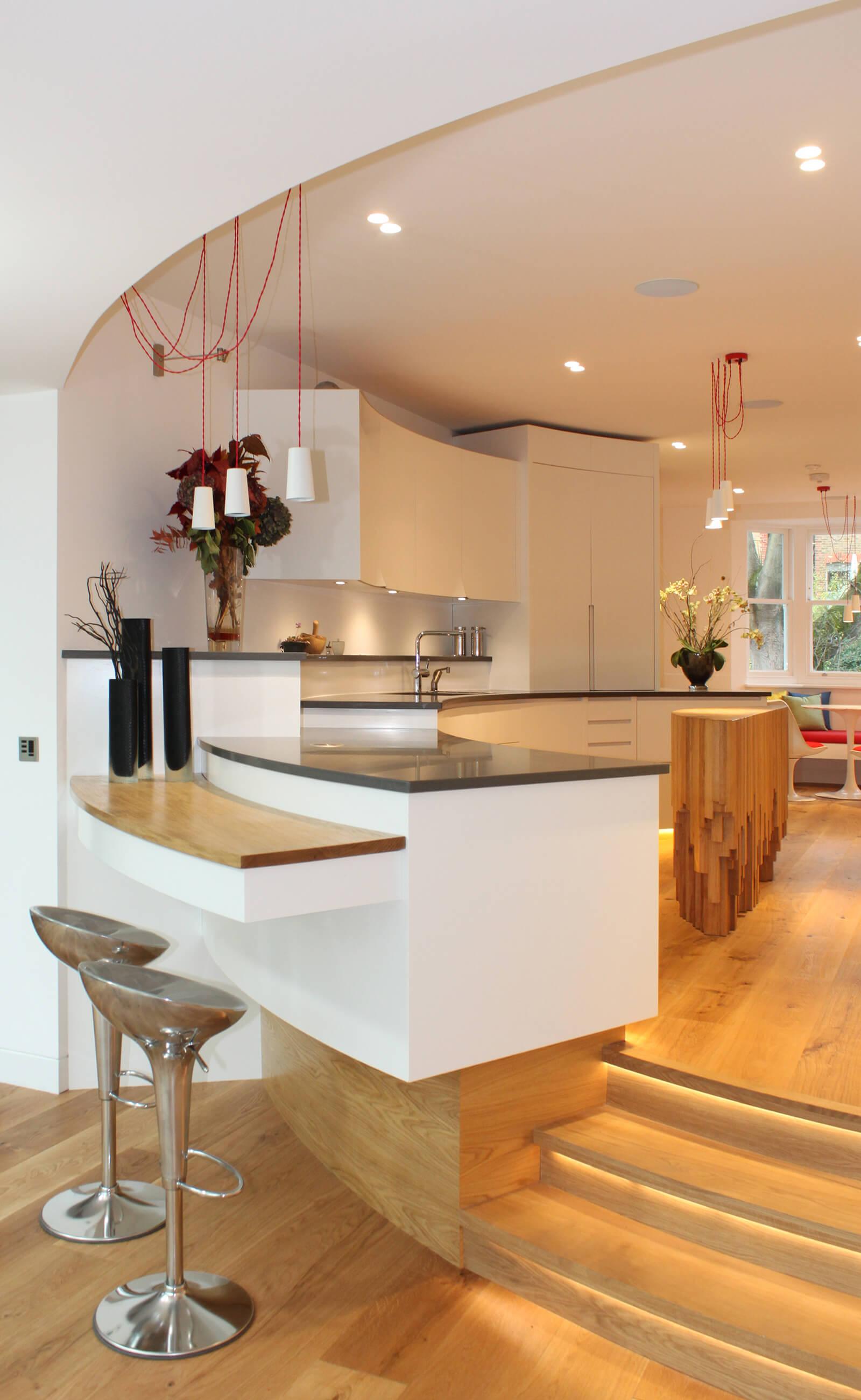 Modern kitchen design over a split level with sculptural kitchen island.