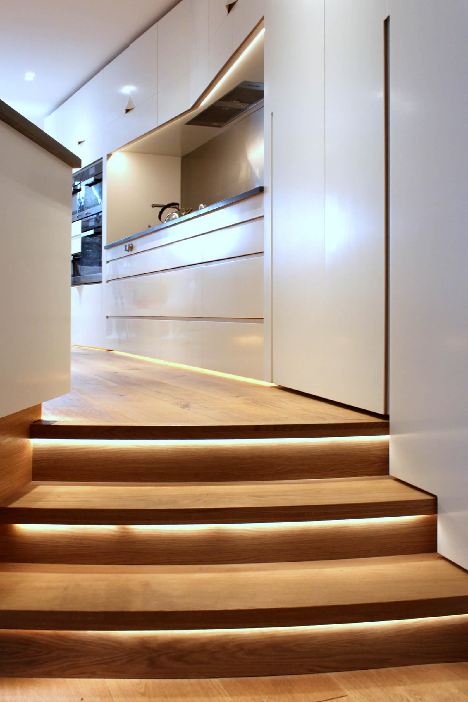 hidden led lighting on steps in white and oak kitchen designed by Splinterworks