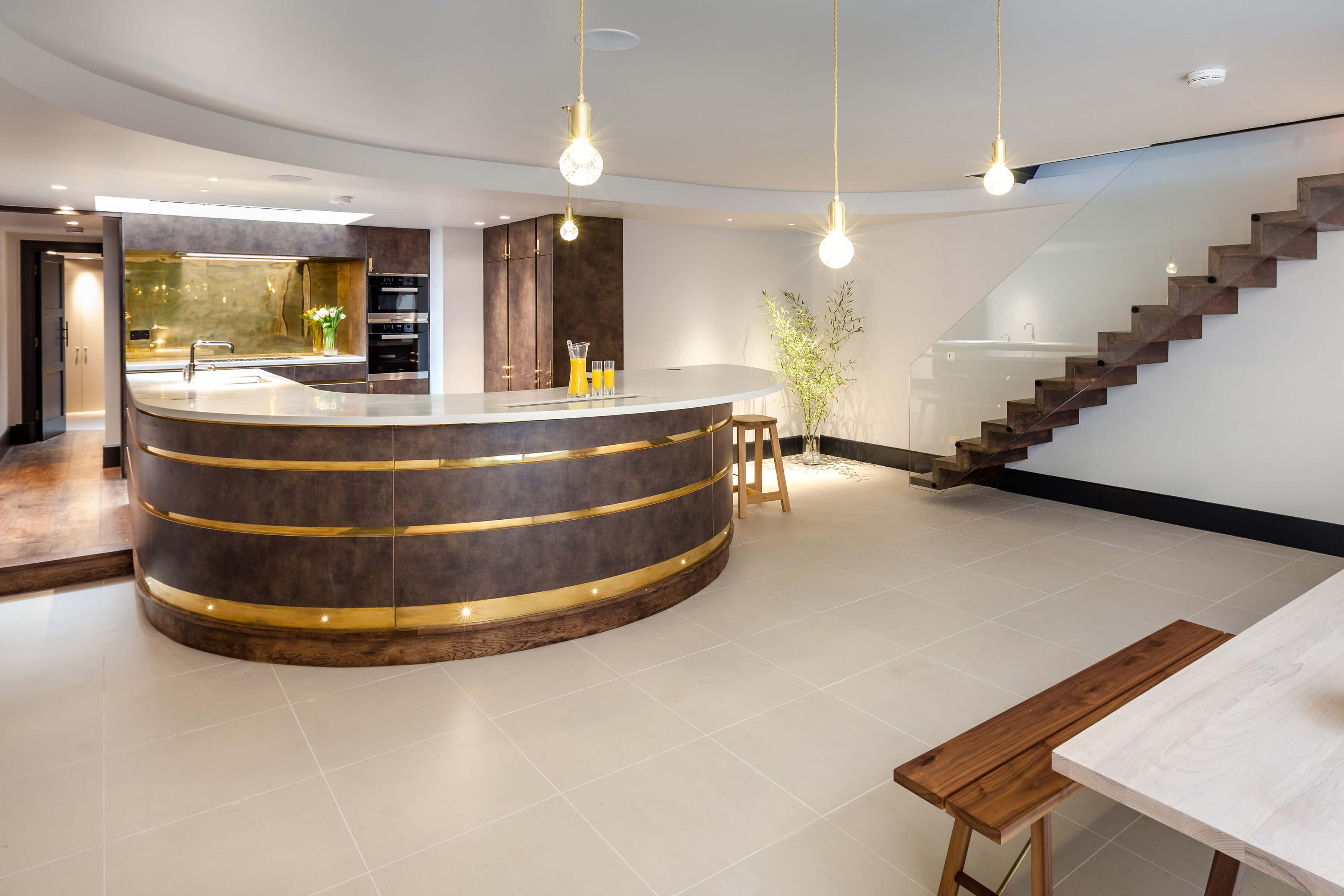 Basement kitchen with dark kitchen cabinetry and brass detail