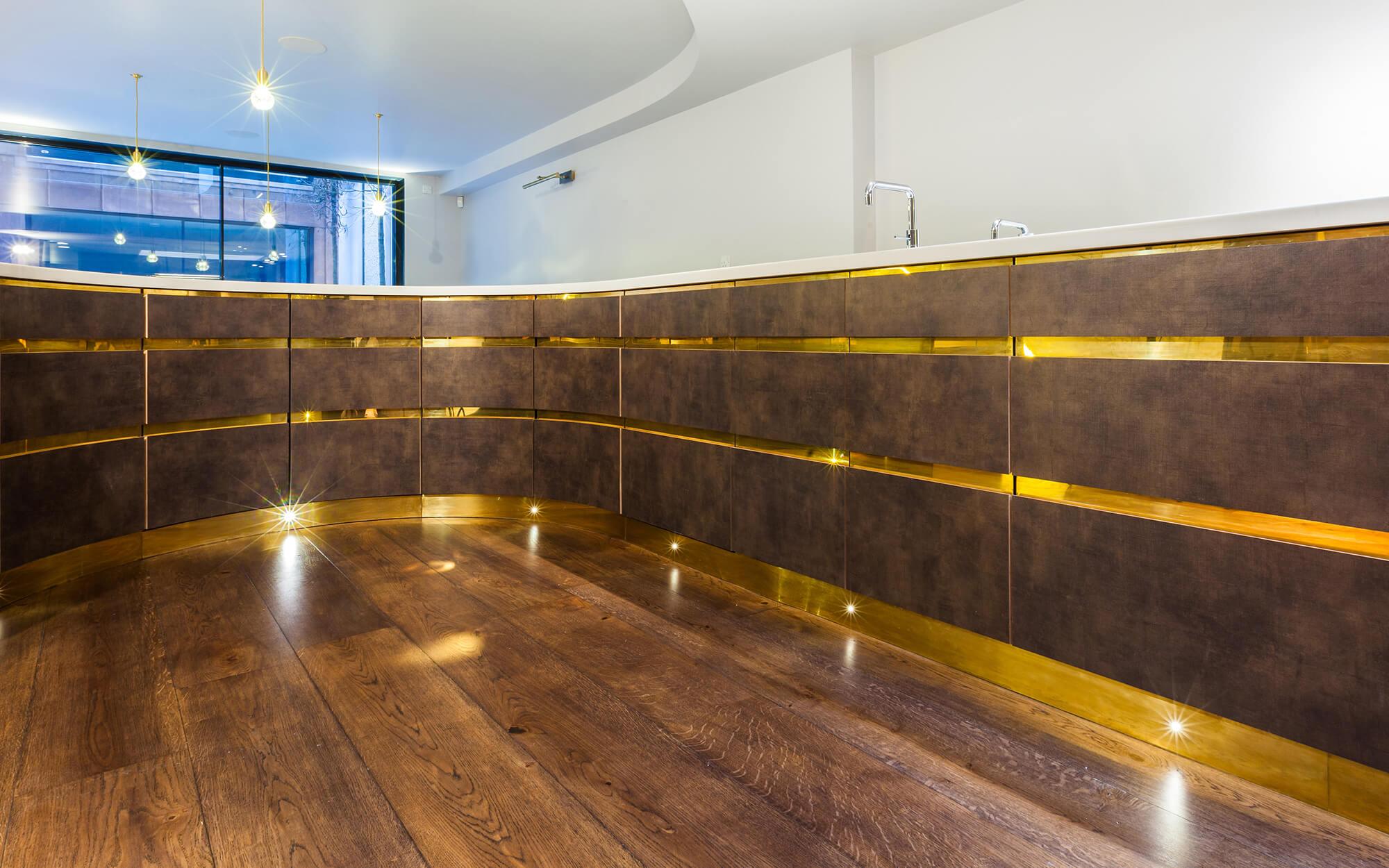 Clever hidden storage in luxury kitchen with brass details and brass kick-board