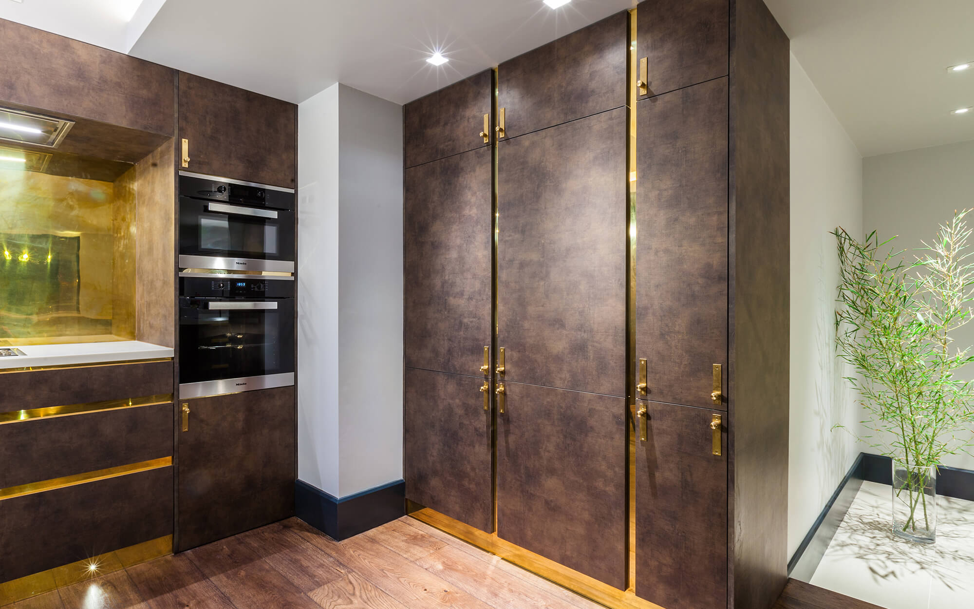 Dark kitchen cabinetry with brass detail and clever storage