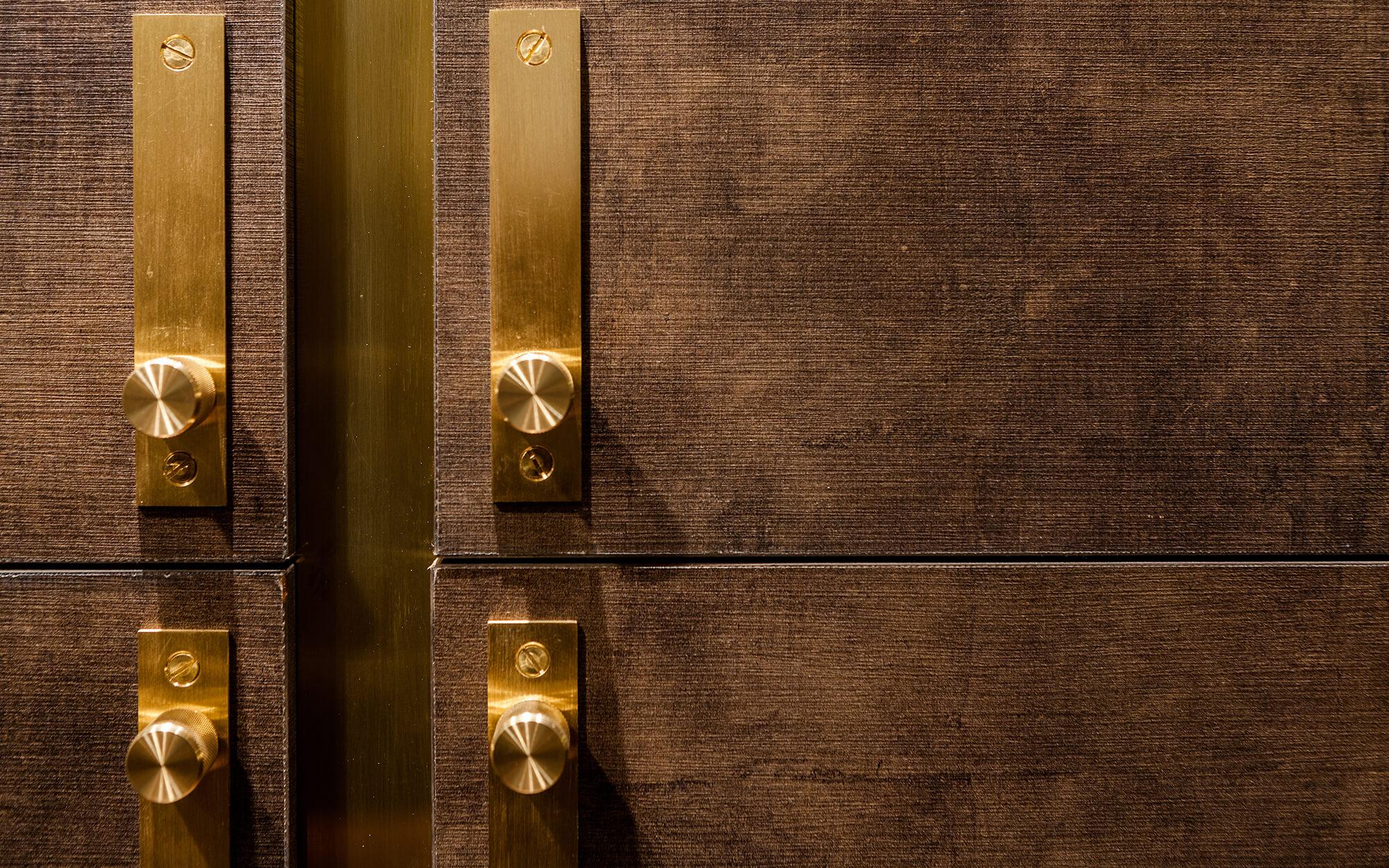 Brass trim on dark brown kitchen cabinetry custom built by Splinterworks