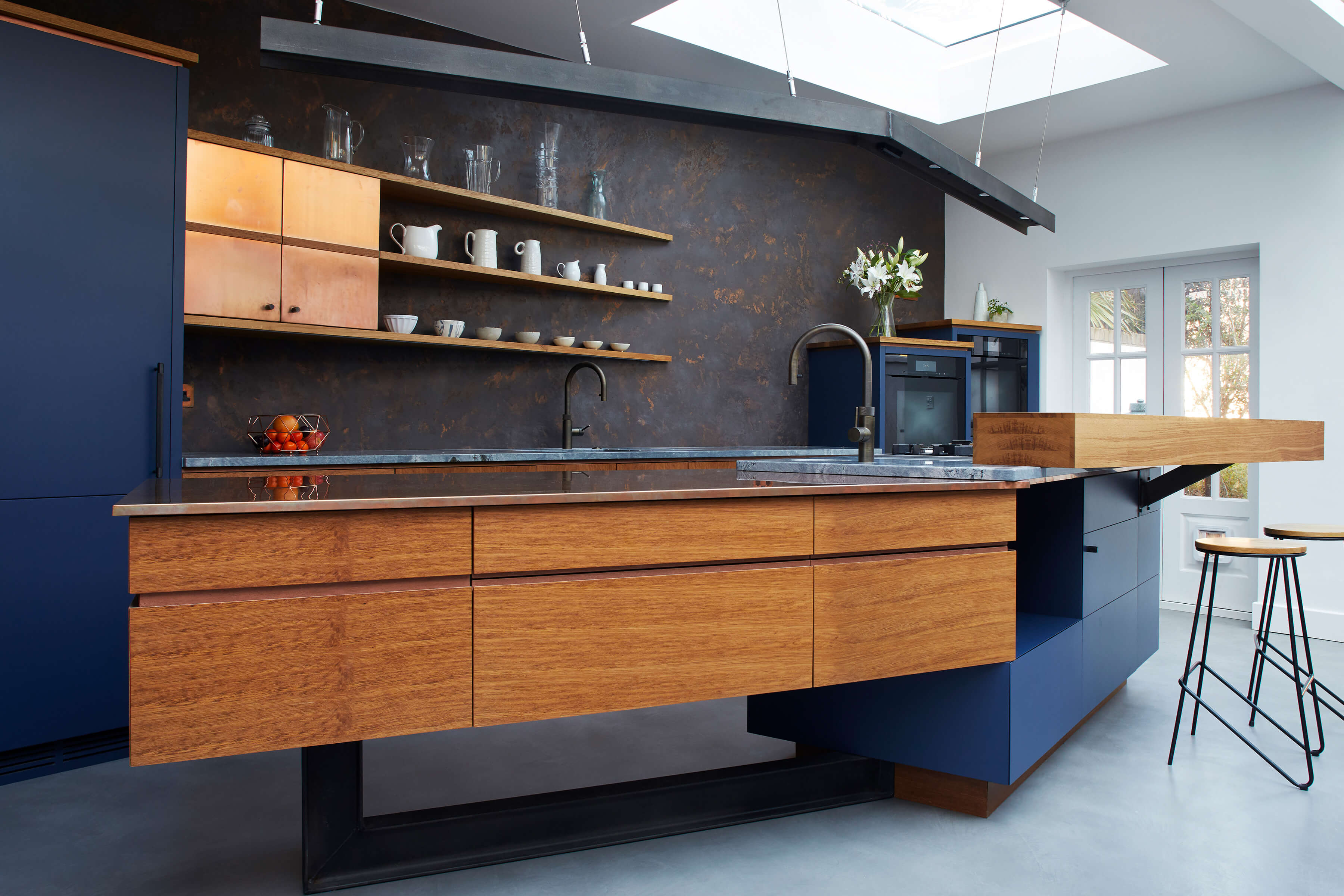 Blue and copper metal kitchen with clever storage and ergonomic design