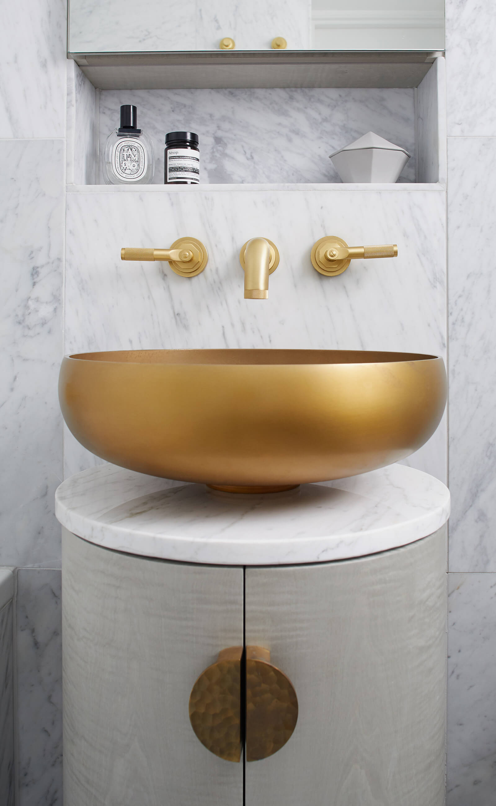 Round brass basin on grey bathroom cabinet with carrara marble walls