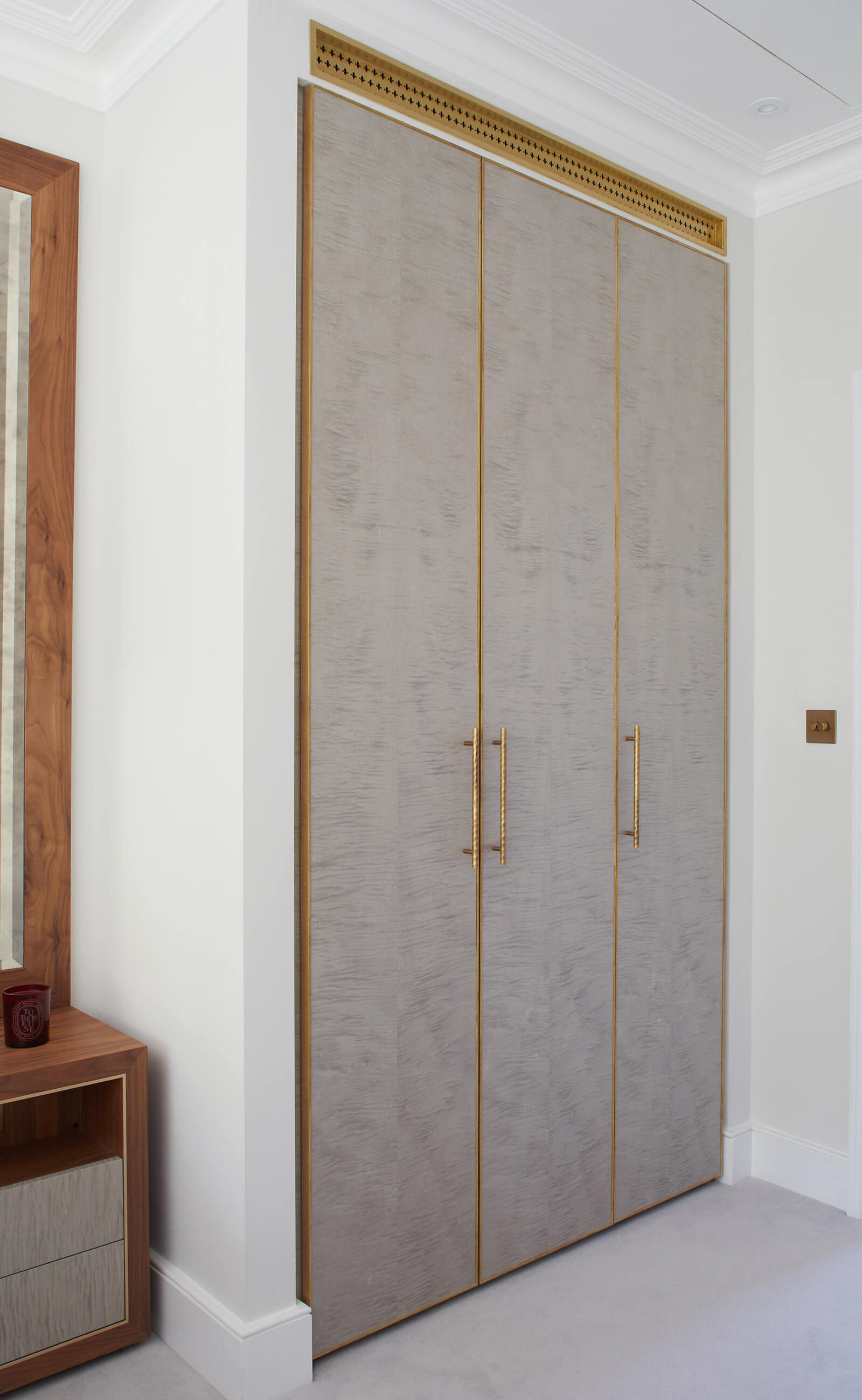 Custom built in wardrobes in sycamore with brass details in a calm serene bedroom
