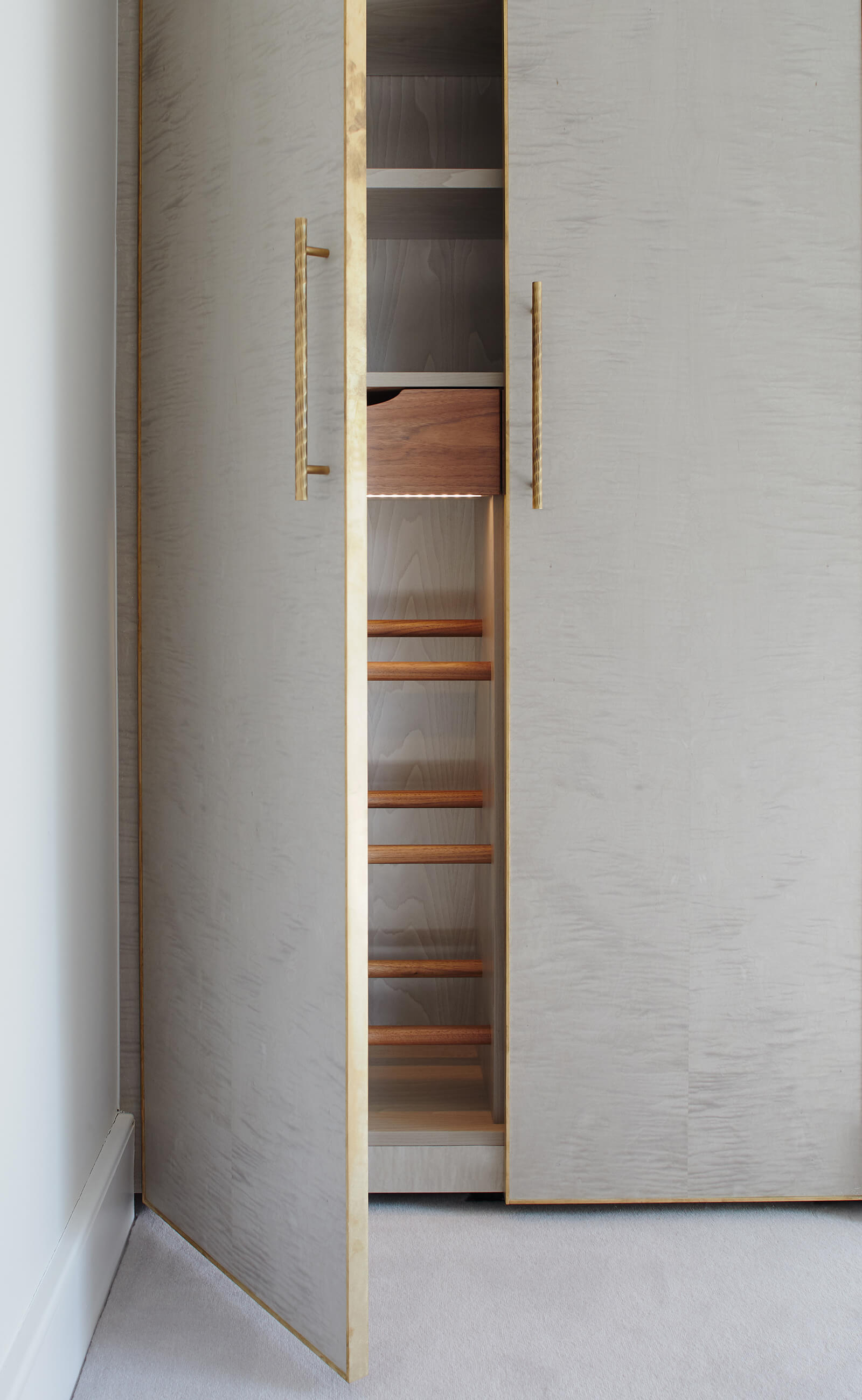 Wardrobe doors with delicate brass edging and custom built shelving in walnut.