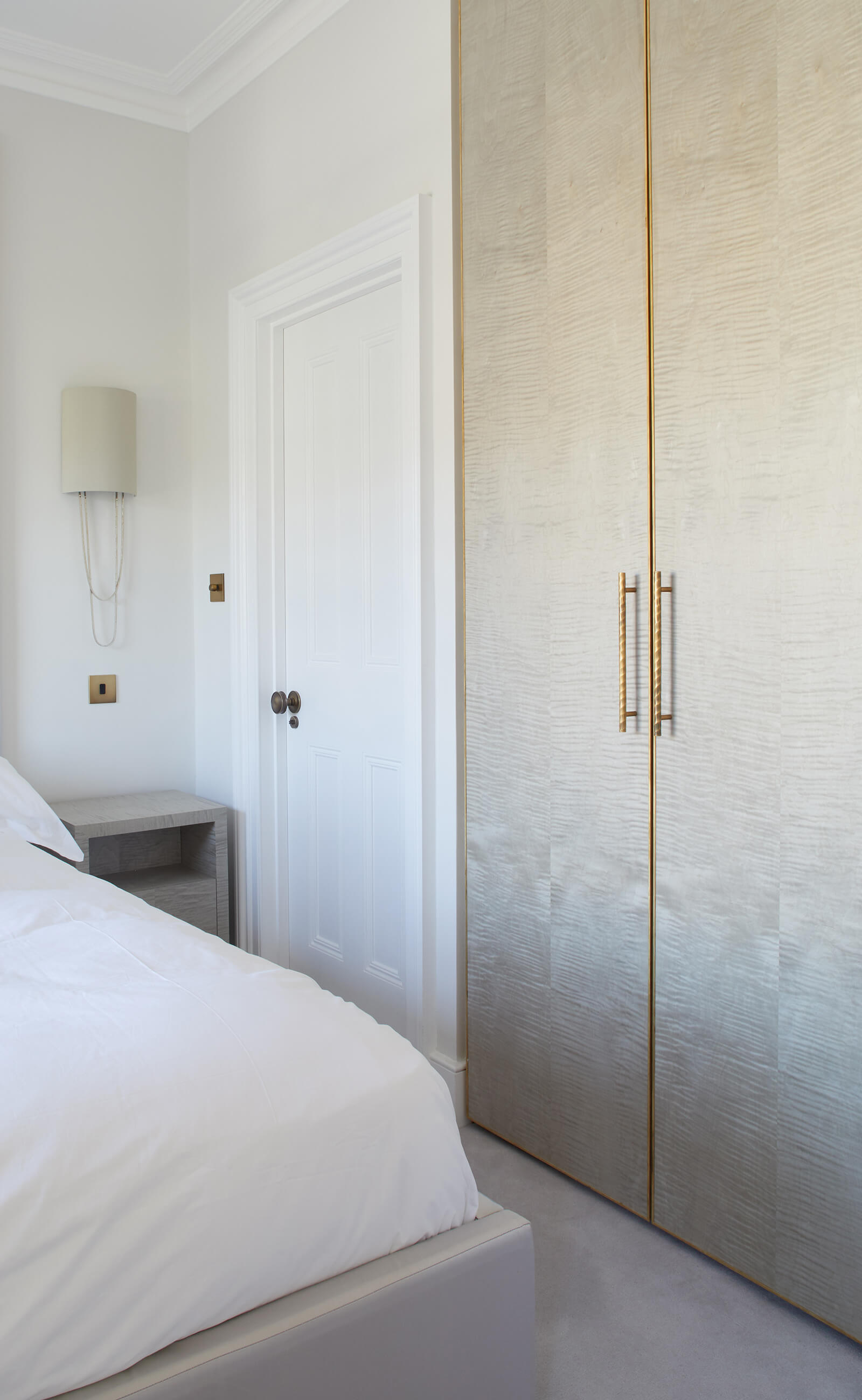 Custom wardrobe cabinetry with brass detail in a serene bedroom