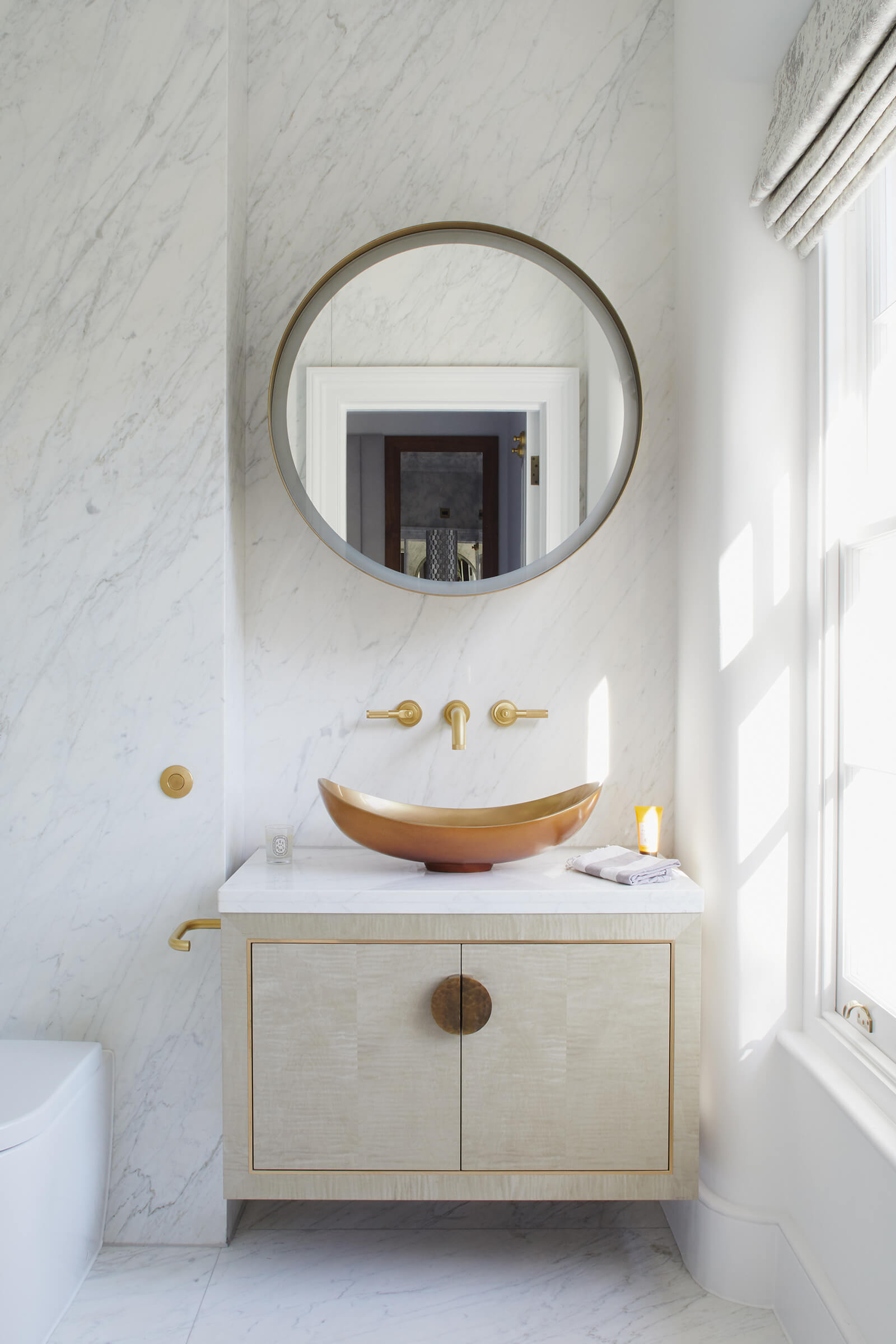bathroom vanity cabinet with brass details below a brass sink in a carrara marble bathroom