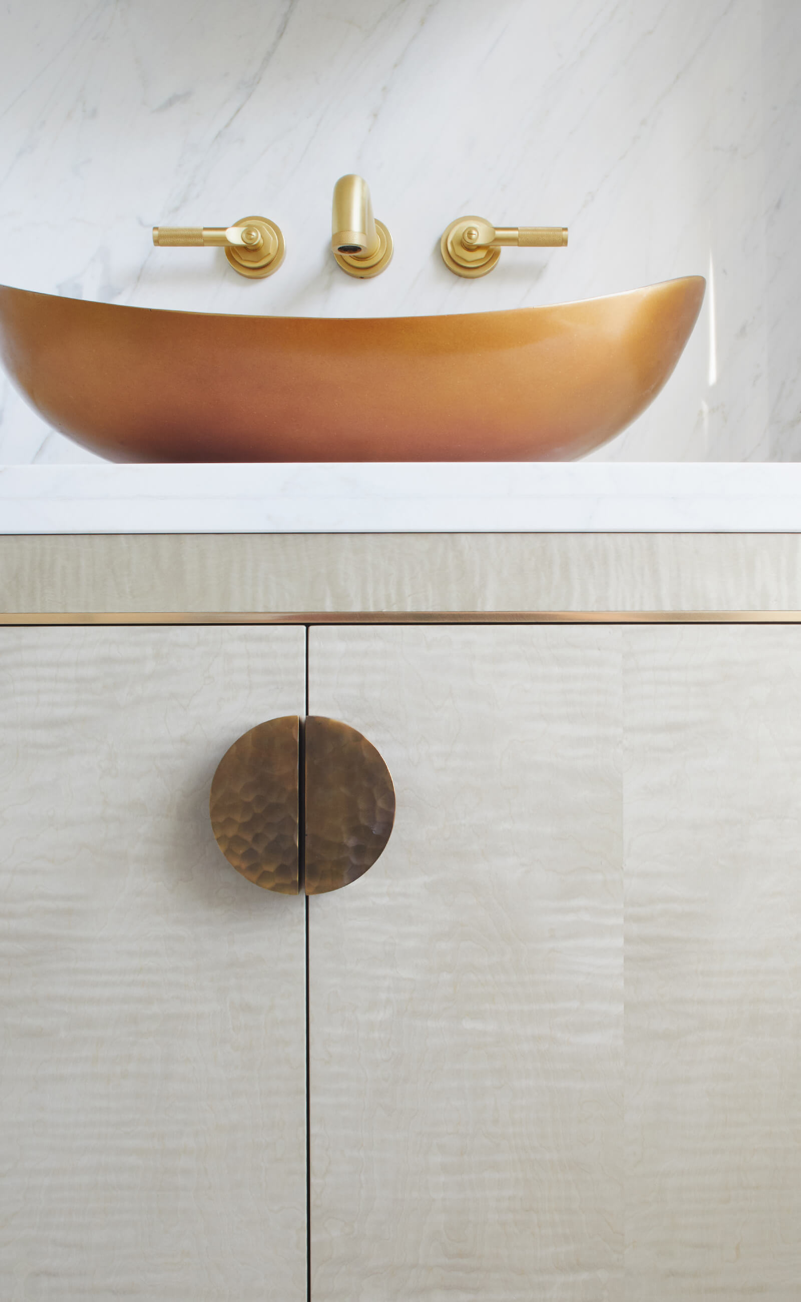brass basin on veneered bathroom vanity cabinet by Splinterworks in carrara marble bathroom