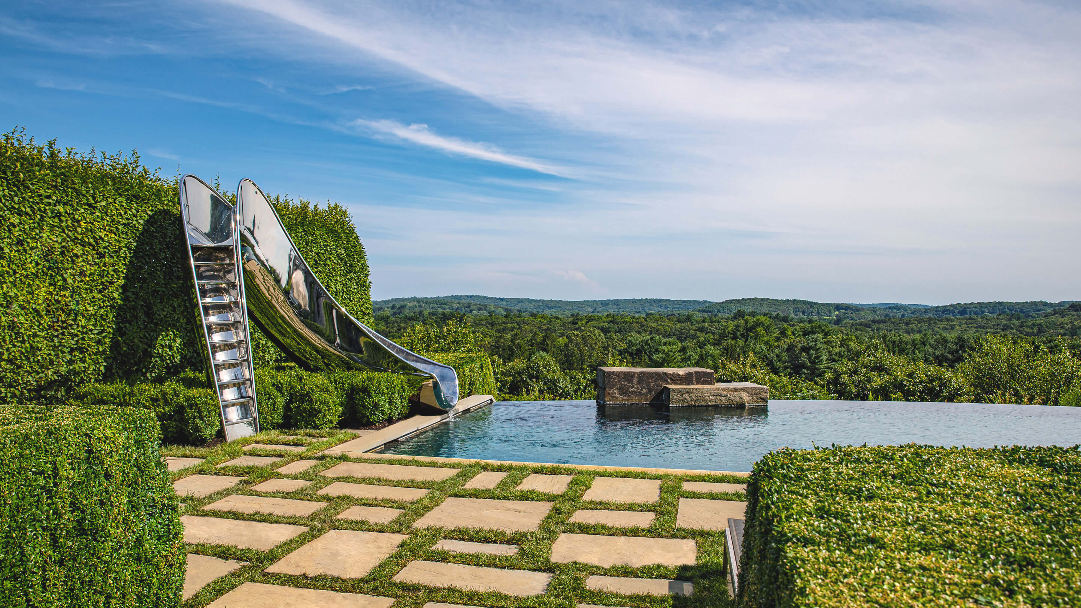 Luxury water slide next to beautiful infinity pool in up state New York.