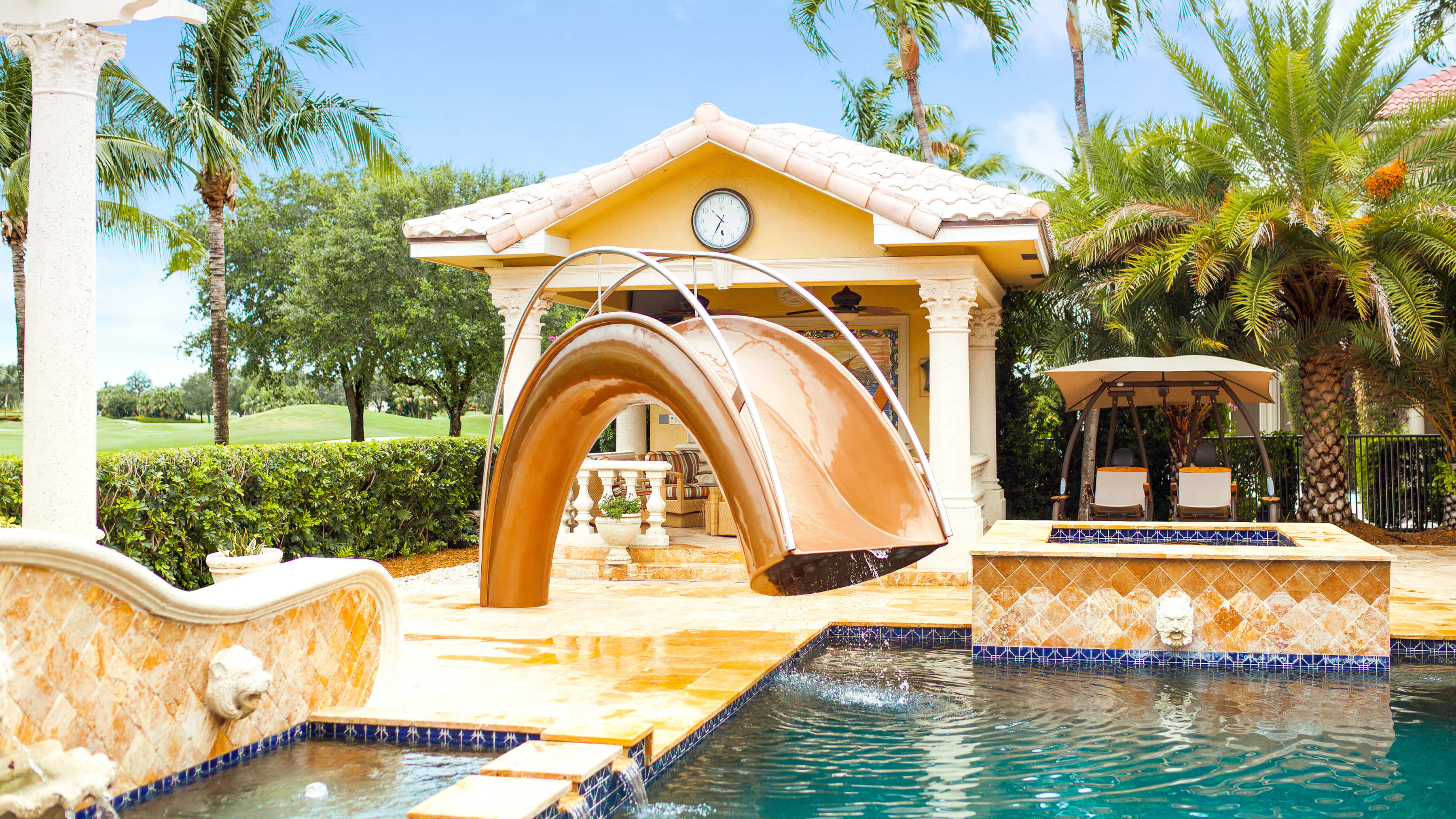 Bronze resin water slide with hand rails in front of BBQ area and palm trees.