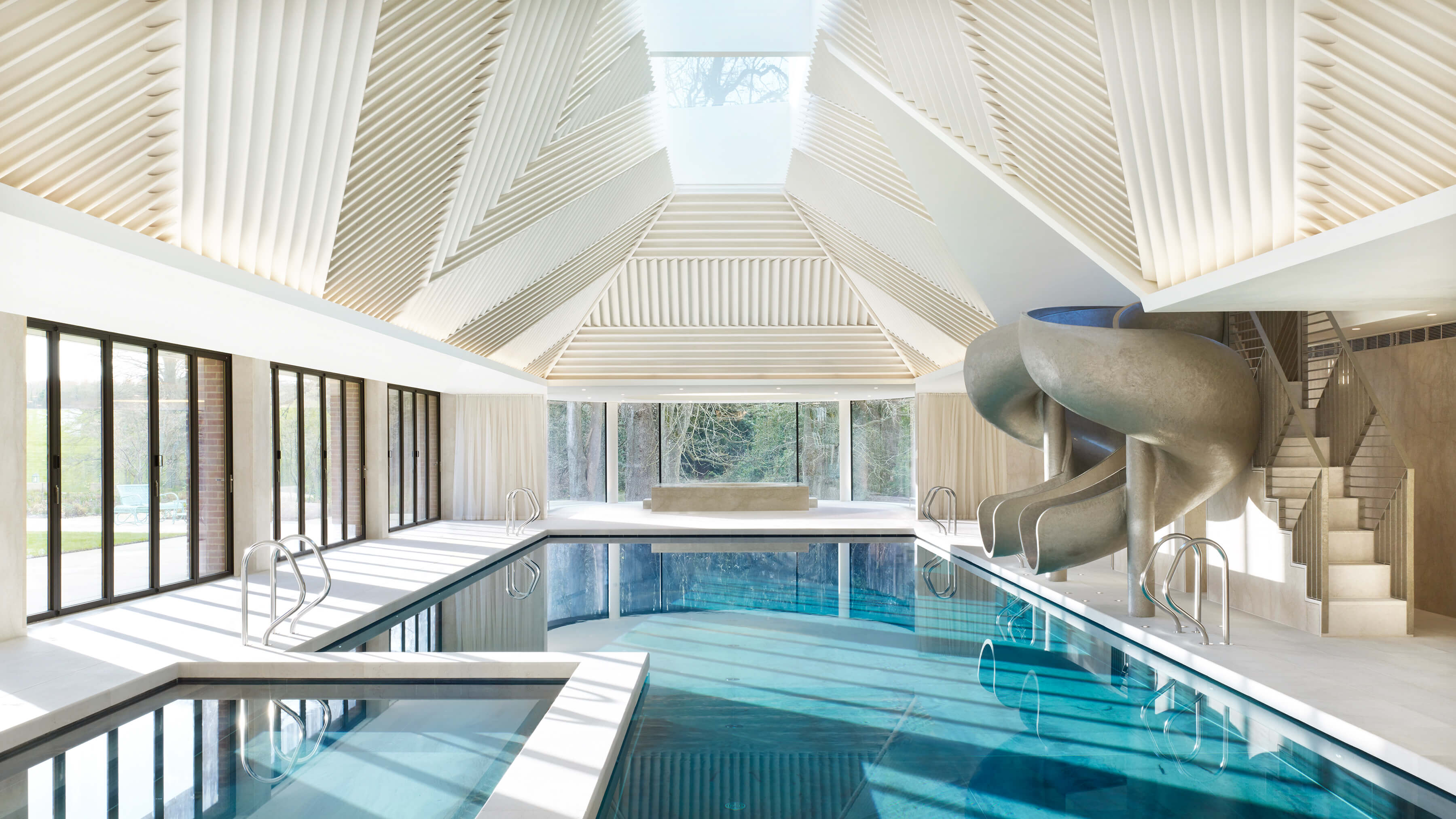 Metallic gold resin pool slide by Splinterworks in spectacular pool pavilion with sky light.