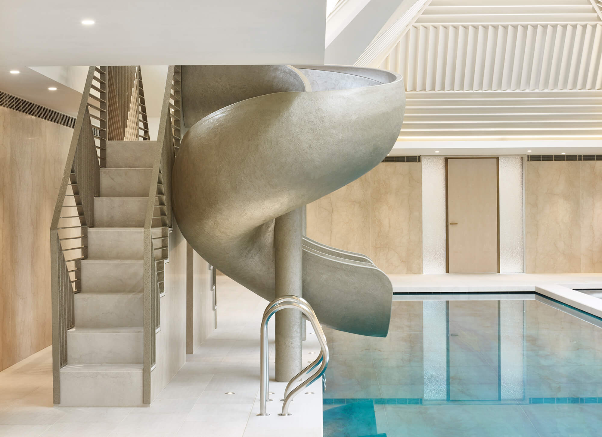 Luxury gold swimming pool slide with steps beside an indoor pool.