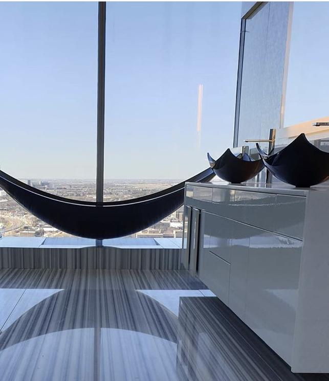 Black hammock bath and twin black basins next to full length window