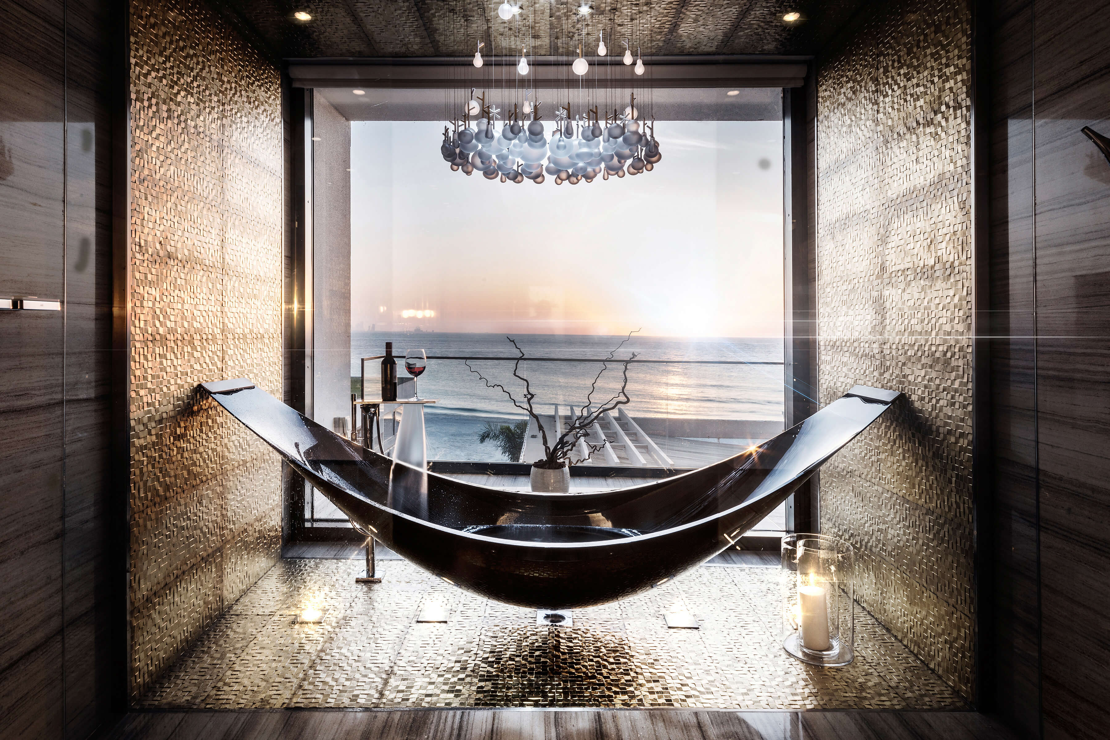 Black hammock bath in luxury hotel bathroom with sea view and a chandelier