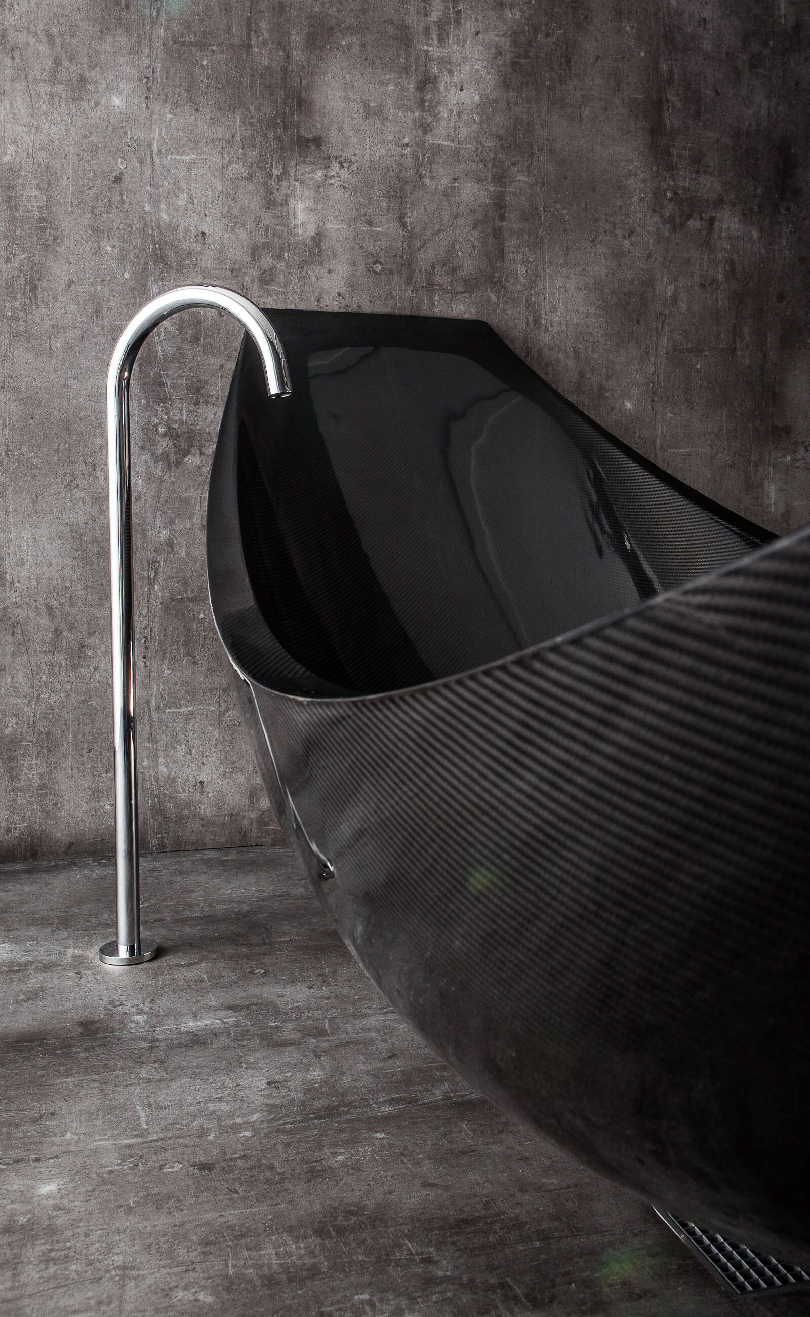 Detail of floor standing bath tap next to black suspended bath in polished concrete wet room