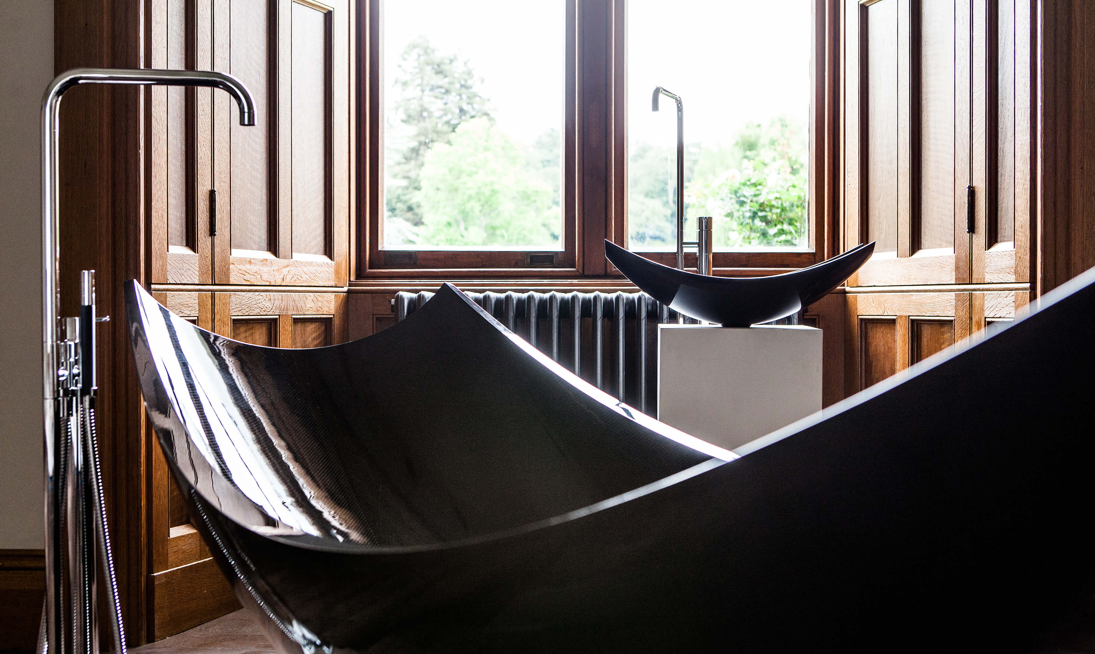 Close up of black freestanding hammock bath and basin next to window.