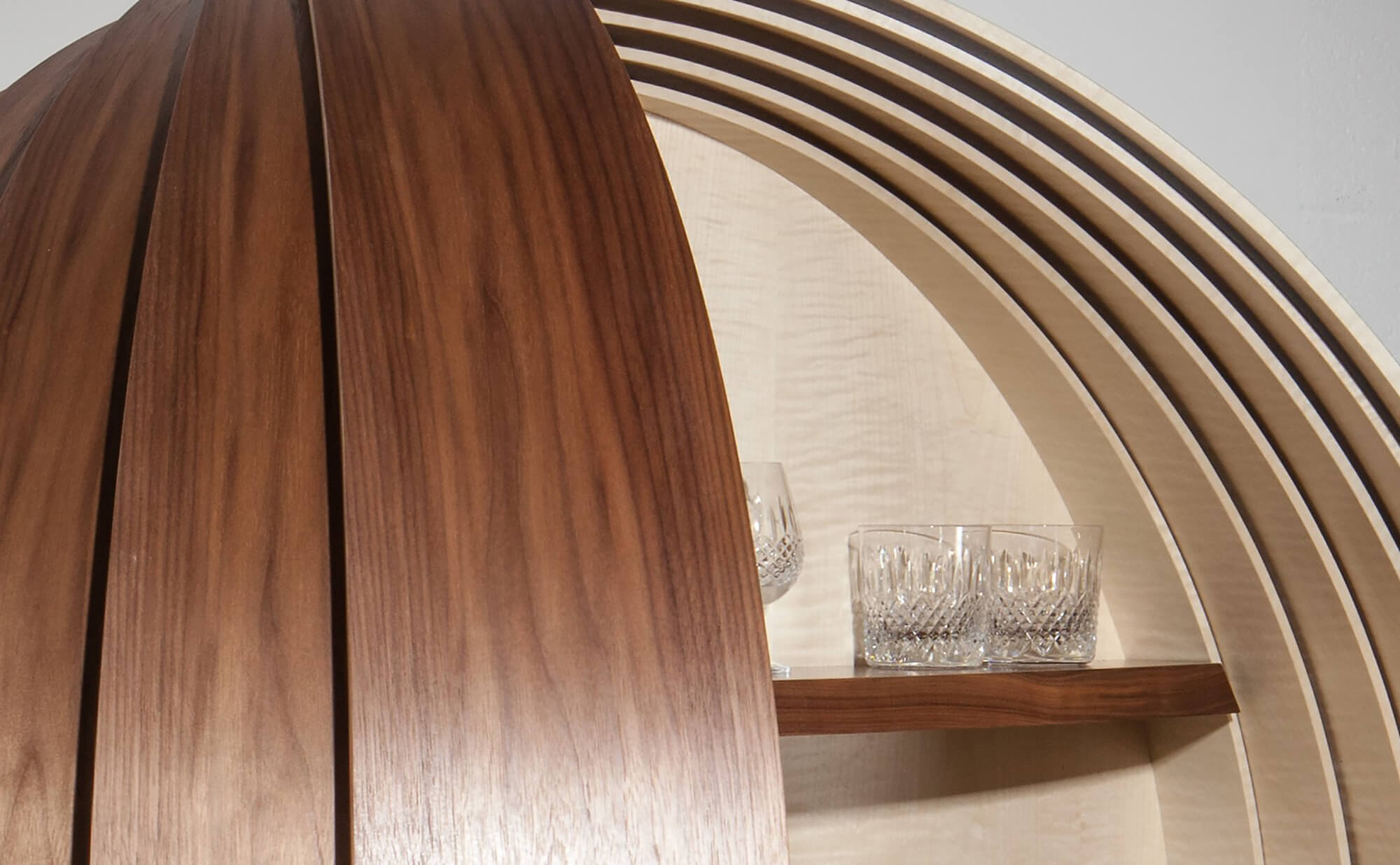 Detail of the luxury Dime bespoke drinks cabinet with crystal glasses on shelf.