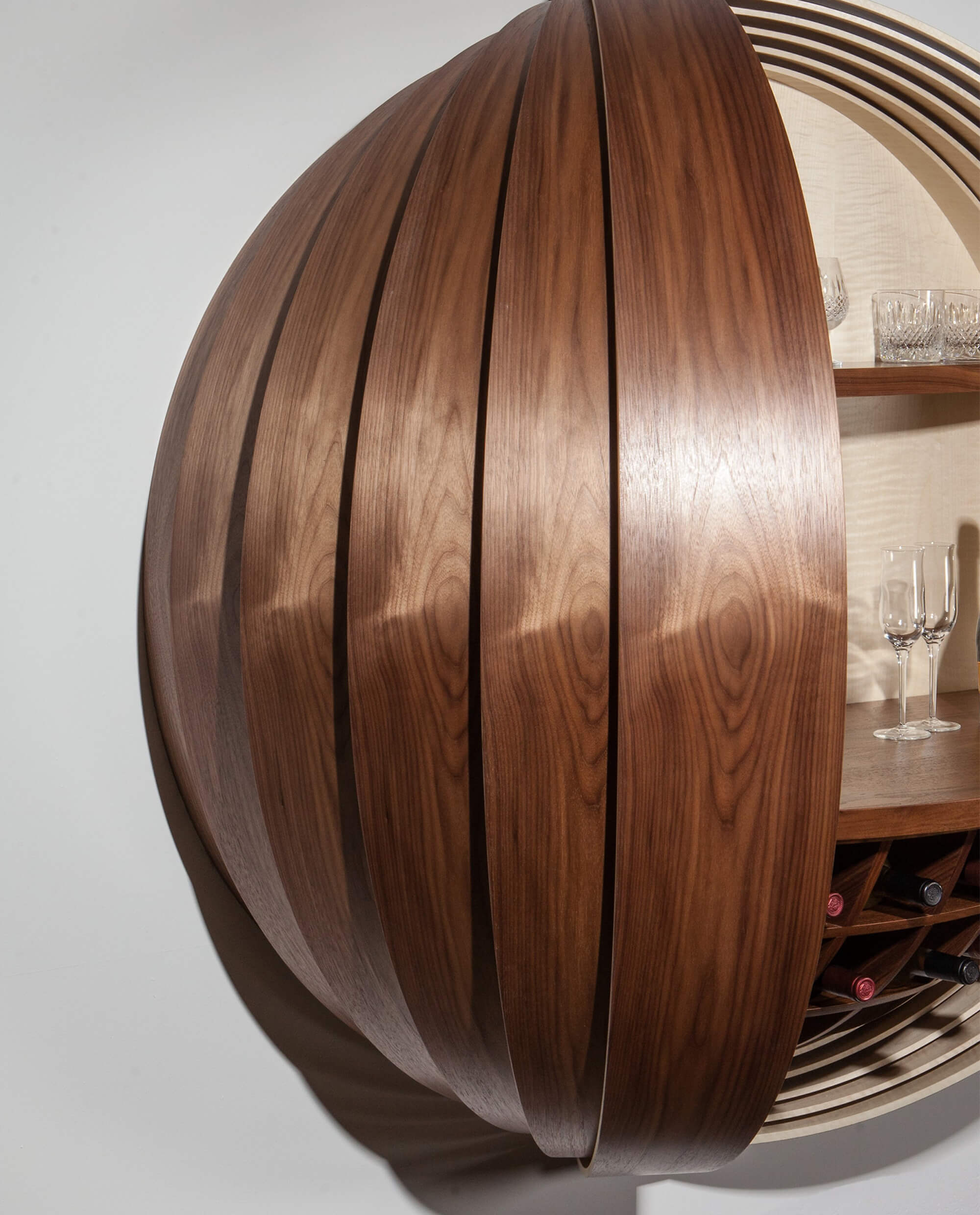 Spherical wall-mounted liquor cabinet with walnut finish.