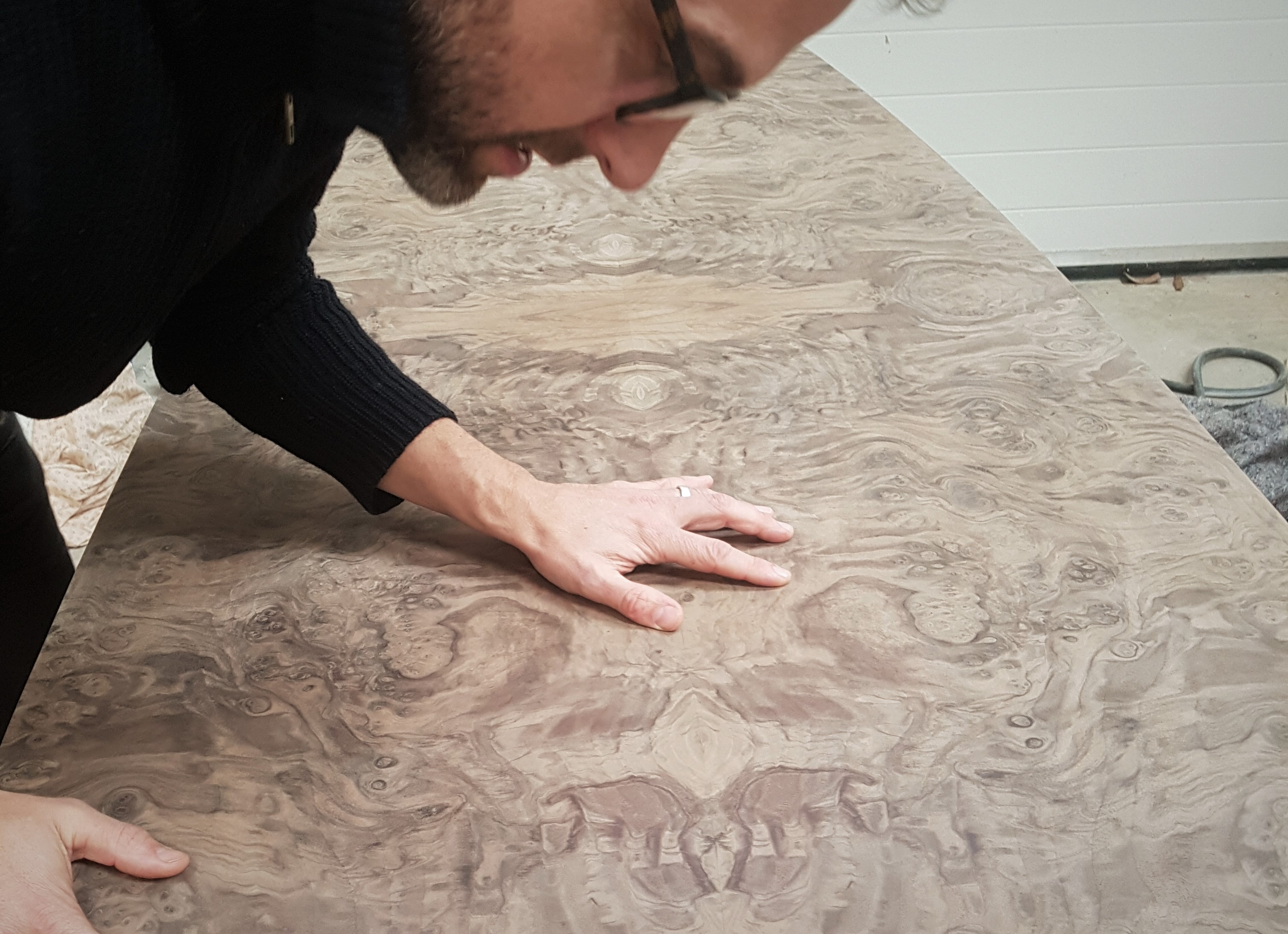 A Splinterworks craftsman examining the unpolished veneer on a bespoke table commission
