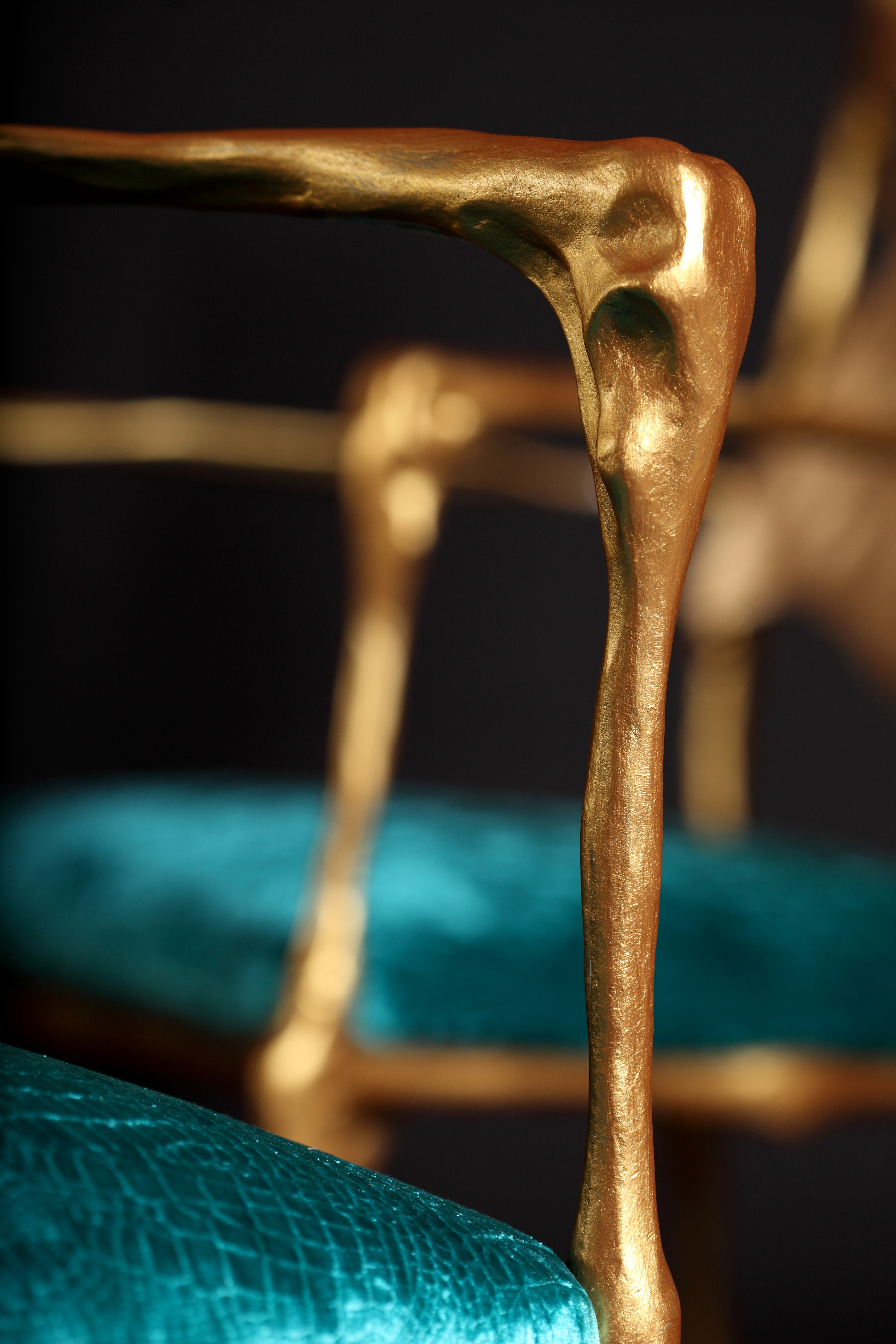 Dali-esq chair with hand sculpted arms in bronze and velvet teal cushion