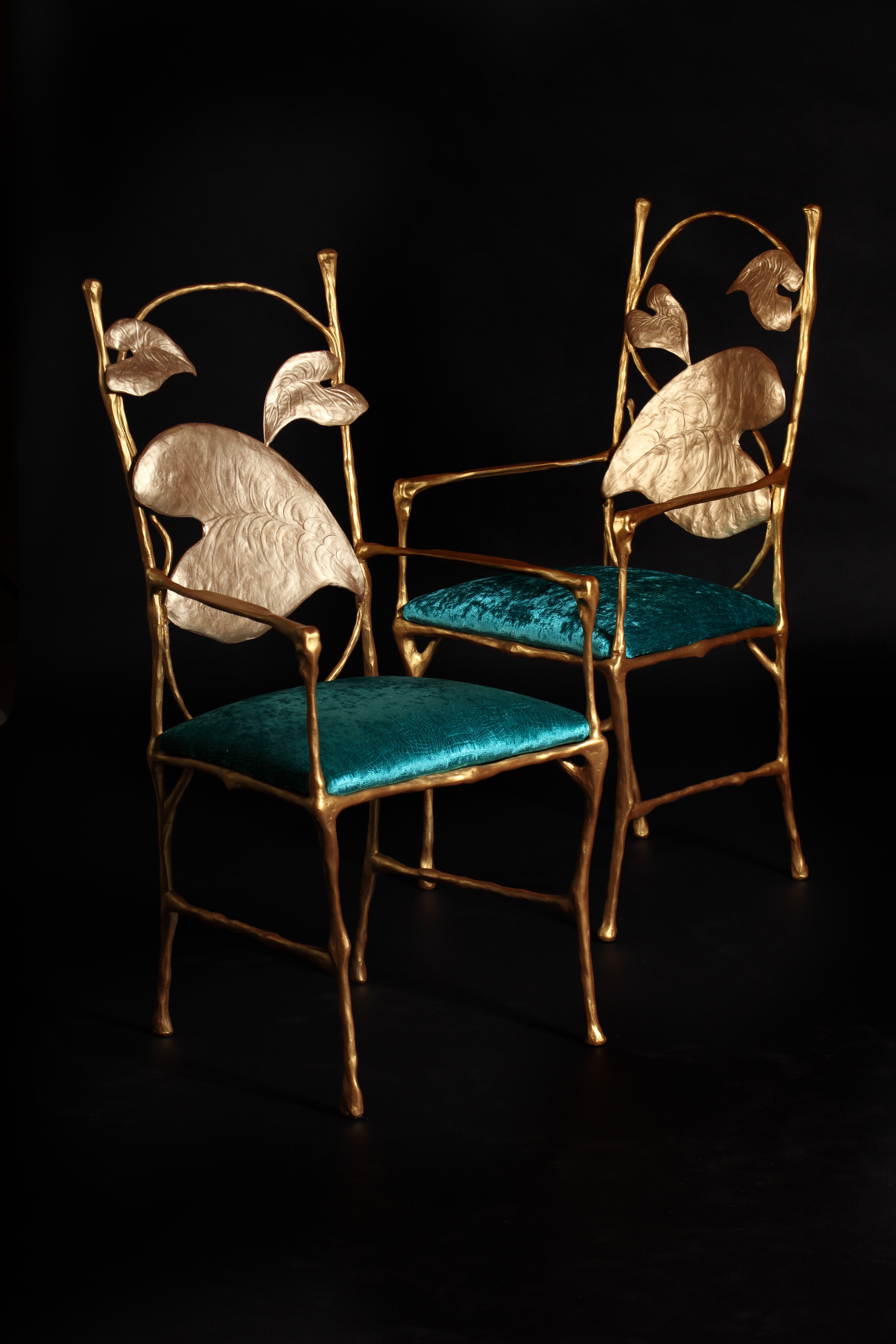 Hand sculpted bronze chairs with teal velvet seats are a bespoke furniture commission by Splinterworks